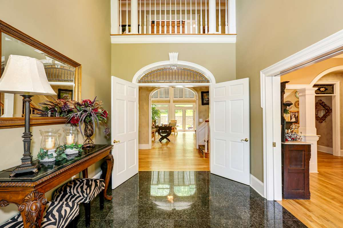 The entrance to this elegant mansion will impress you with its 20 foot ceilings, granite floors and beautiful wood trim molding
