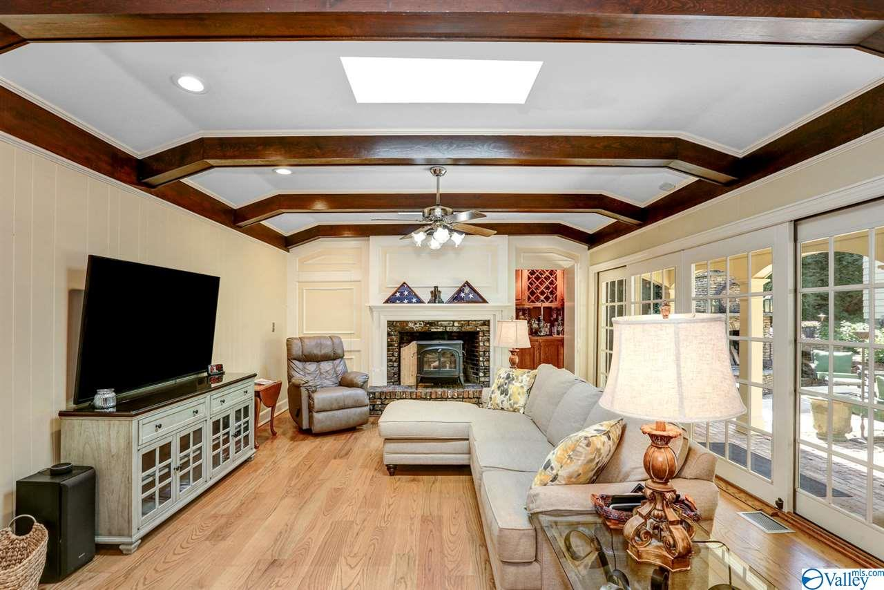 Cozy family room with hardwood floors and wood beamed ceilings with FP and wall of sliding glass doors to the outdoor entertainment spaces.