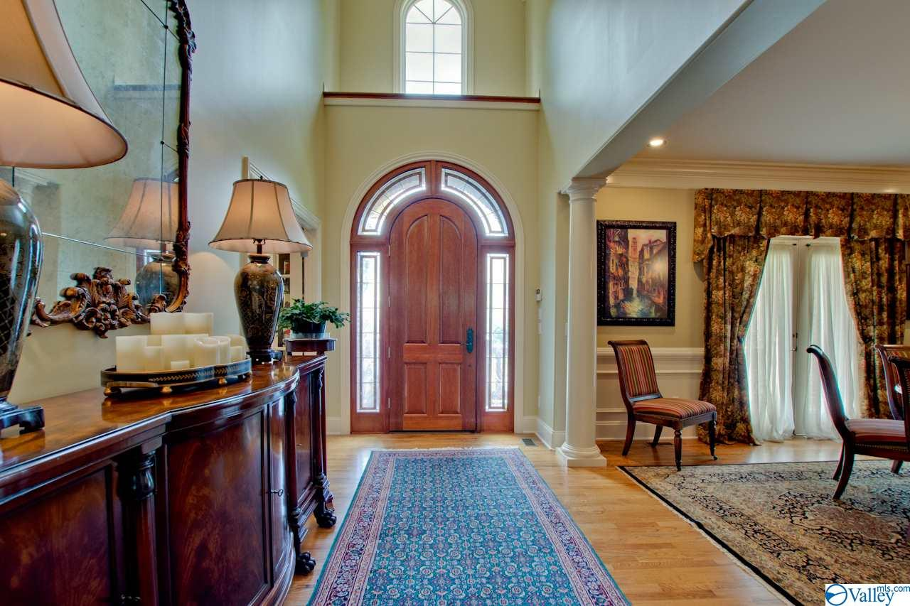 2 Story Foyer features hardwoods, detailed moulding, and chandelier lift.