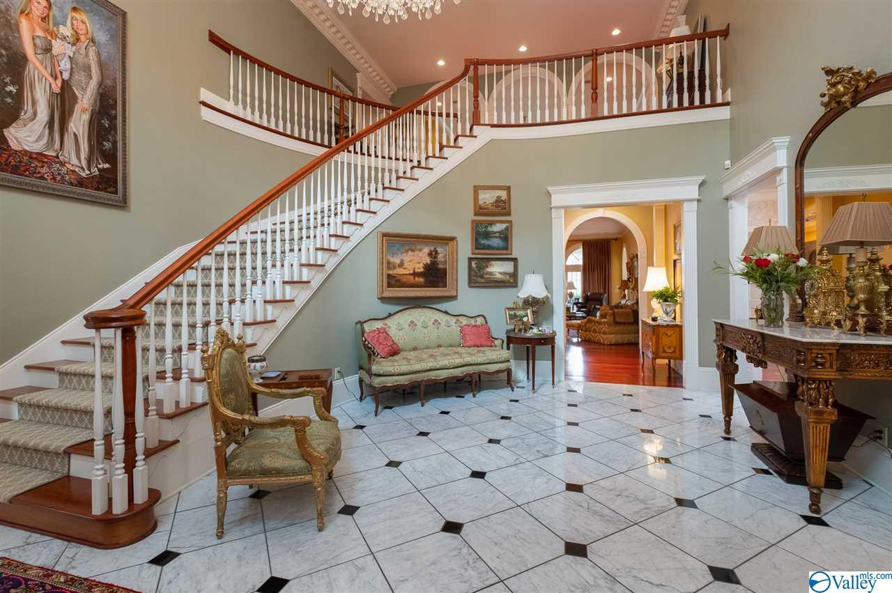 The foyer and staircase are the dramatic focus of the grand entrance.