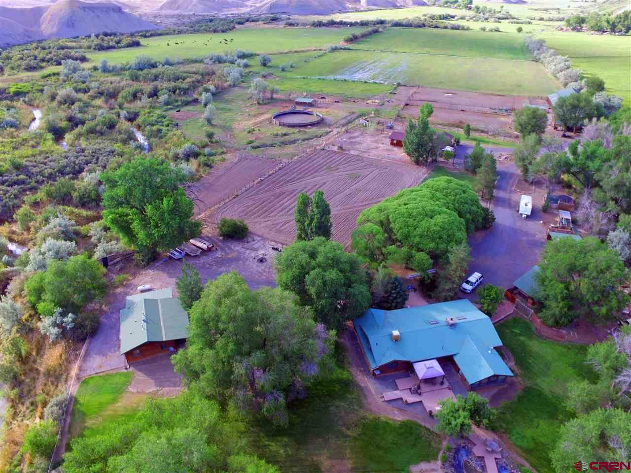 4 Dwellings on this 69 irrigated acres for a total of 6273 square feet of living space which includes 9 bedrooms and 7 baths, as well as a bunkroom that sleeps up to 8 or more. House#1 has 2083sqft, 2bed/2bath, House#2 has 2310sqft., 3bed/2bath. House#3 has 800sqft, 2bed/1bath and House#4 has 1080sqft., 1bed/1bath with downstairs bunkroom and bath. Completely setup for horses and cattle including a 120x180 arena, round pen, cattle chute, tack room, stalls, etc. Buyers would have room for themselves and lots of quest. Currently House #3 is rented month to month. Possible Property Use is endless for this little piece of Paradise so use your imagination.