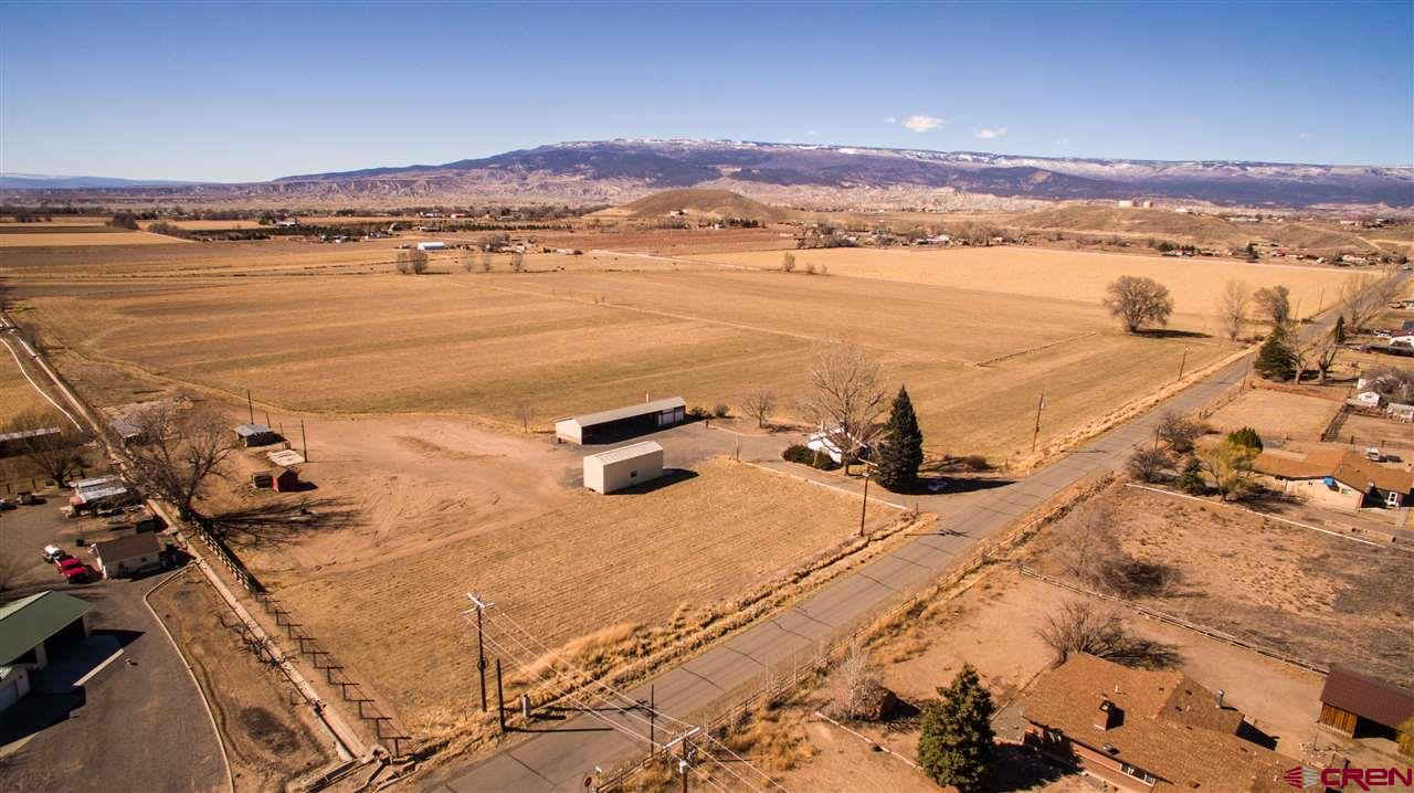 This lovely 37-acre farm has it all! The cute farmhouse features an open floor plan, roomy kitchen, covered patio and a nice basement for storage plus a fruit room and/or wine cellar. Its landscaped yard invites with mature shade trees, automatic sprinklers and 360-degree views of Grand Mesa, the West Elks and the San Juan mountains. The garage holds your motorhome or boat or 2 cars and the 4-bay equipment shed gives you 2 more garage spaces. The house has a new electrical panel and newer furnace and hot water heater, and garage and equipment shed sport new roofs and new metal siding. Well-maintained irrigated fields have concrete ditches and are completely fenced. A second water tap allows you to build a second home.