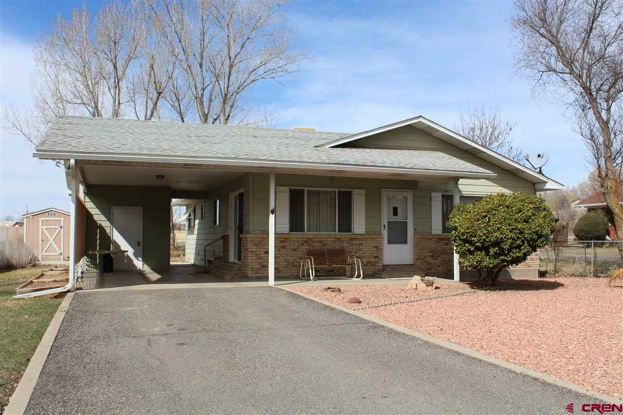 """Beautifully and well kept and well built 1980 home. Privacy fenced to the North. Carport plus two storage sheds. Raised garden beds and scenic backyard. Walking distance to downtown Hotchkiss and across from Willow Heights park. Free standing gas stove supplements winter heating. Newer interior updates. <a href=""""http://www.listingsmagic.com/166533"""" target=""""_blank""""><b>Click here for virtual tour</b></a>"""