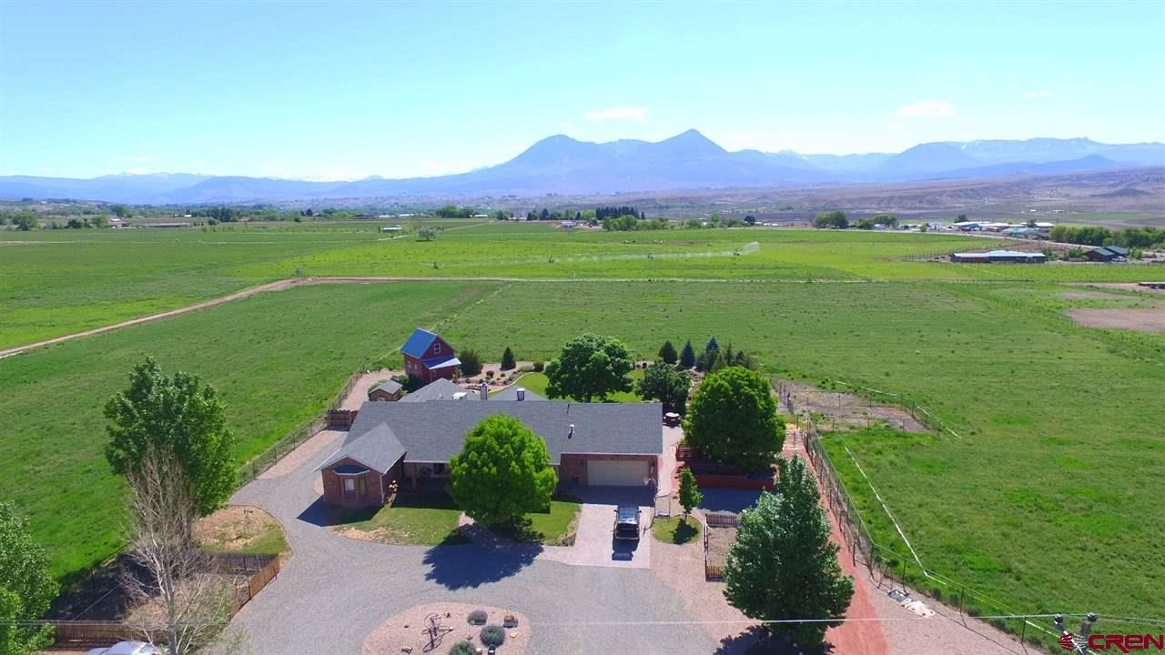 Immaculate small farm on the edge of beautiful Rogers Mesa!  The turn-key operation features two residences, a guest house, numerous well-maintained outbuildings and ample irrigation water.  The 5BR/3BA main home is open and bright. Large windows capture the glorious mountain views and brand-new hickory and oak cabinets, quartz countertops and stainless appliances complete the spacious eat-in kitchen.  The backyard is an entertainer's dream with huge patio, outdoor kitchen, firepit and fountain. The yard is shared by a guest house with kitchenette, loft bedroom, sink and composting toilet, water, power, heat and cooling. The 2BR/2BA original farmhouse's many updates include a new kitchen and bathrooms.  It has its own water tap, large yard and septic system. Outbuildings consist of a 45x36 tractor shed with three large sliding doors (could easily be a horse barn), pole barn, small loafing shed, 3-bay loafing shed with cattle chute and corrals, Quonset hut garage/shed and an insulated shop building. The irrigation water is applied via gated pipe and center-pivot and big gun sprinklers.