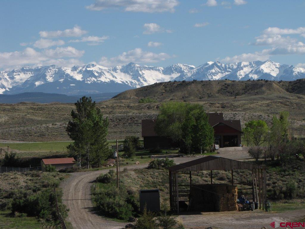 59.6 acres with 27 irrigated and 9 shares of Uncompahgre Valley Water User water. This 2700 sqft, 3BD/4BA brick home is nicely finished with tile and hardwood floors, aspen walls, walkout basement, large laundry room complete with heated towel rack, wood stove and spacious kitchen.  The land is irrigated by a gated pipe system for easy irrigation and has been setup for horse boarding, hay production or use for your own livestock. Complete with 3 stall barn, loafing sheds, round pen, shop, hay barn and dog kennel. Sitting on the top of a small hill the home has fantastic views of the San Juans and over looks the hay meadows and wildlife ponds. The BLM joins the property to the South for unlimited riding or hiking. Nice private setting but close to town.
