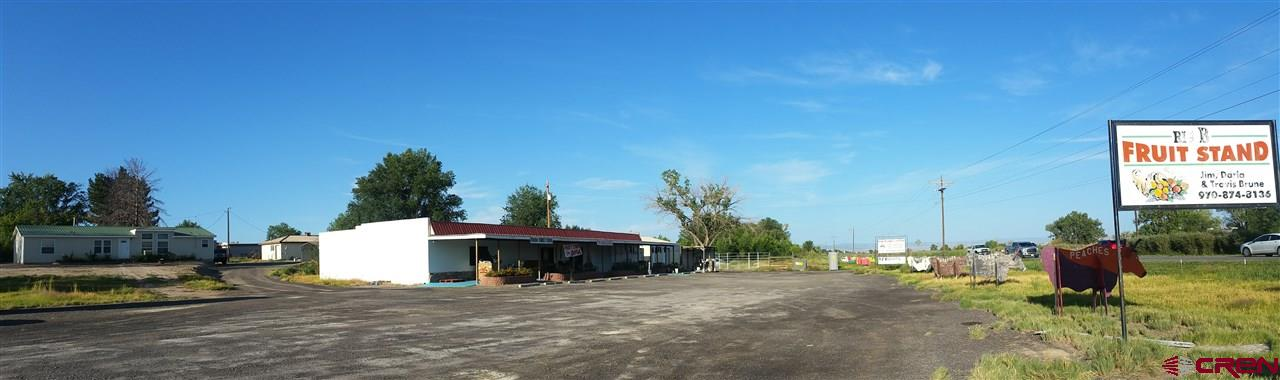 ESTABLISHED PRODUCE MARKET + HOME + FARM GROUND + MAIN HIGHWAY FRONTAGE = TONS OF POTENTIAL! WHAT A GREAT SET-UP! THIS PROPERTY IS BEING SOLD TOGETHER WITH THE ADJACENT PARCEL (SEE MLS #750760) WITH A 1620 SF HOME, OUTBUILDINGS & FARM GROUND WITH IRRIGATION. SO MANY POSSIBILITIES HERE WITH AN AWESOME LOCATION! Established Produce Market PLUS Very Nice Home PLUS Farm Ground! Grow your own produce or HEMP or HOPS, the new up & coming profitable crops, on the Farm Ground. The 3456 SF Commercial Building with a Large Refrigerated Room, Huge Parking Area and Main Highway Frontage enroute to many of Western Colorado's Scenic Areas, makes this a Prime Spot that offers TONS of possibilities! Take advantage of the abundance of traffic that goes by here! Continue with the Current Business, Expand on the Idea, or Make it something entirely different - the choice is yours! Perfect for an Art Gallery, Studio, Locally Hand-Crafted Arts & Gift Shop in addition to the Produce or other items. Most of the FF&E in the Commercial Building is included (list on associated docs or will be sent upon request). There is also an additional Large Storage Building on this property, along with 2 more Cooler Units. Also included is a Tractor. If you don't want to live in the home, you could lease it to a Caretaker or Manager.