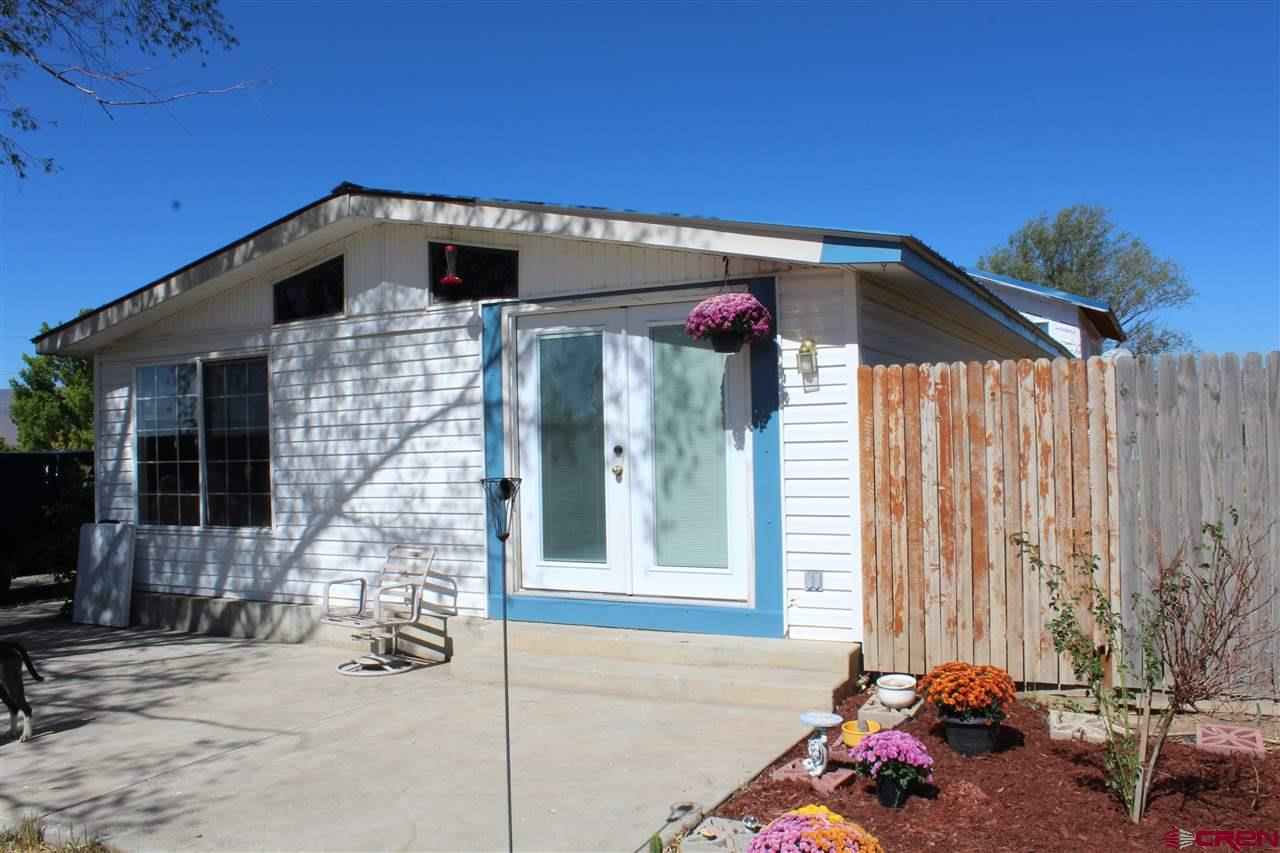 Great starter home on Lamborn Mesa with plenty of water rights for the entire property and more. The views of Mount Lamborn are top notch! Newer hot water heater, newer leach field, newer kitchen applicances, washer and dryer are included and hot tub. City has recently replaced the water line from street to tap. RV dump station built in to septic system. Gas line for exterior BBQ. Large room on rear of property with vaulted ceilings and ready for finishing touches. Good opportunity to make this your home sweet home. Third bedroom is non-conforming.