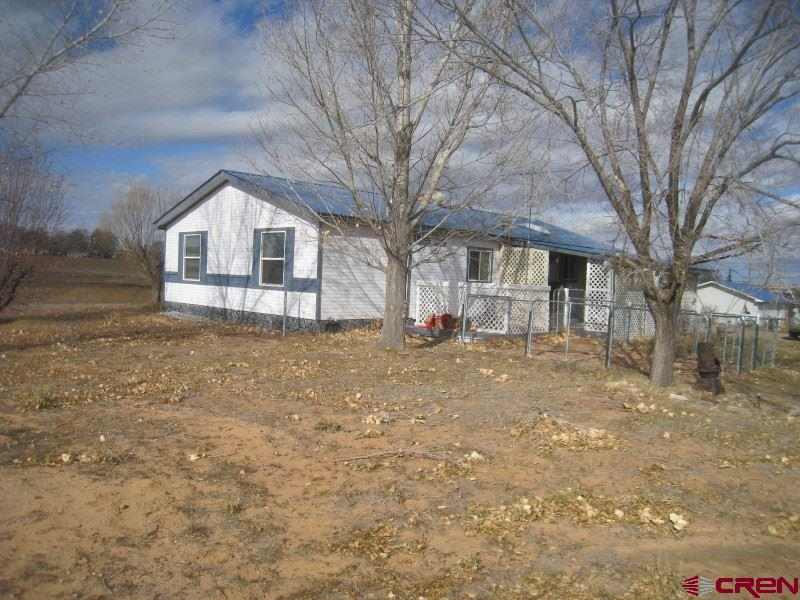 Nicely done 3 Bed 2 Bath Manufactured home that appears to be in great shape and permanently mounted to the foundation. (please take what ever steps that you need to satisfy your questions about the foundation). The home has a very nice floor plan with a large master bedroom suite set up complete separate tub and enclosed shower. The kitchen lays out well and has a breakfast nook and formal dining too. In the spacious living room you'll find vaulted ceilings and a wood stove to take the chill out those chilly winter days.  The covered back deck faces east for relaxing outside and cooling off in the summer while taking in the incredible LaPlata Mountain Range views.  The 30 acres is mostly in production and is irrigated by 8 shares of MVI (comes with the property) and is also supplemented with additional shares all of which is applied through gated pipe. The pastures appear to be in excellent shape and also includes a seasonable pond with a pump that irrigates all of the mature landscaping flowers and lawn around the home. Almost all of the property can be irrigated with the purchase or lease of additional shares of water. The 24' X 26' detached garage/shop is 90% percent finished and is just lacking interior paint and trim is insulated, contains it's own power panel, concrete floor along with 1 overhead door and 1 entry door. The 36' X 40' barn has power, a finished tack and saddle room, hay storage, 4 stalls and separate corrals, potable water and a loft mezzanine storage. The property is fenced and crossed fenced, PRIVATE, NO COVENANTS and INCREDIBLE VIEWS.