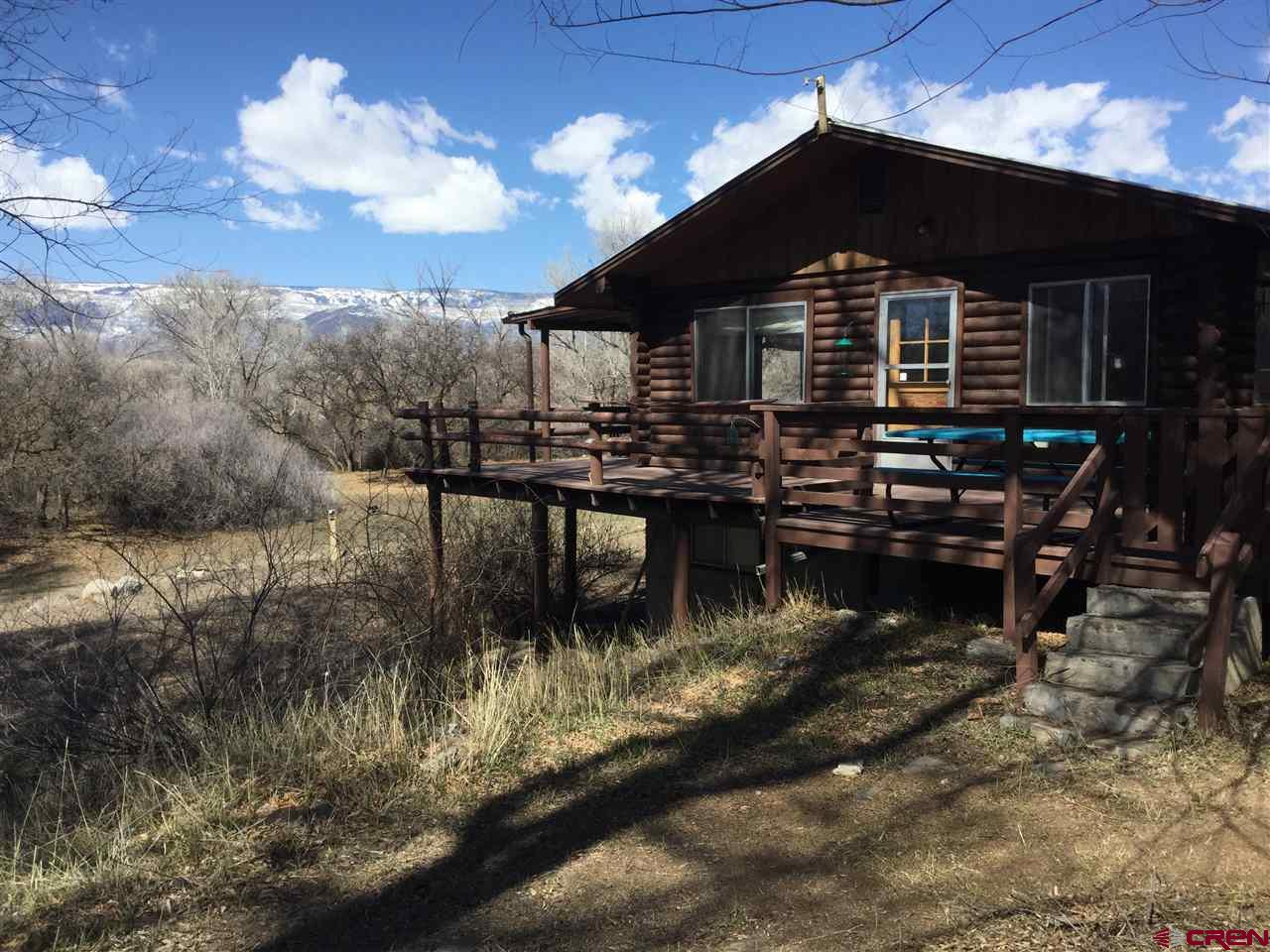3bd/2bth Log home with a wrap around deck and walk out basement on Surface Creek! The home sits on 1.28 acres with creek frontage and Grand Mesa views. Lots of wildlife travel through the property. Newer engineered septic has been installed. Home is in good shape but needs some updating. Basement Bath was remodeled in 2015. Plenty of room for parking along with a detached 2 car garage. Nice private setting in the back yard with the sound of Surface Creek and the natural landscaping make this a nice Oasis.