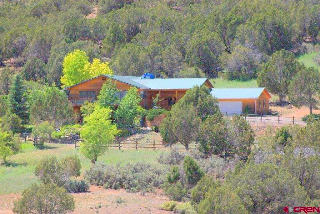A perfect blend of solitude and easy proximity to town! Two spacious homes with fabulous views of the West Elk mountains grace almost 49 secluded acres on Powell Mesa just north of Hotchkiss. The 4BR/3BA main house features two large decks, professional landscaping, formal dining, a family room and a billiards room with table included. An especially nice master suite comes with its own sitting room and a bath with walk-in shower and soak tub. The 3BR/2BA second home has a bright open floor plan and several picture windows. This unique property includes a 36x36 detached garage/barn/shop, is bordered by BLM and is known for the abundant big game and other wildlife making a home in its rolling wooded hills and meadow.