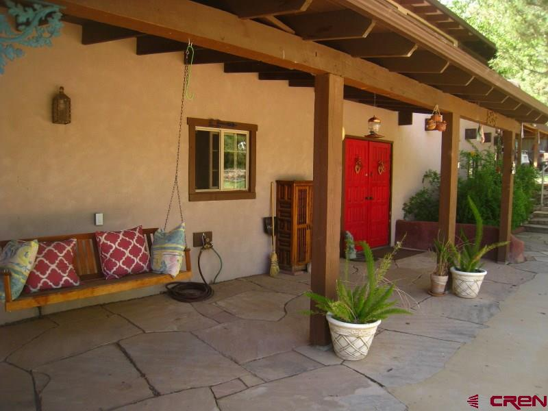 Eclectic Charm in McElmo Canyon!! Be the grower of your own fruits and vegetables. Be the Lord of your own Hobbit House. Be Quiet and Peaceful nestled in the cottonwoods with privacy and splendor. Be what You want to be and where you want to be in Picturesque McElmo Canyon. Allow yourself to explore the 2400 square feet of this spacious and self sustaining home on 3 Acres graced by flagstone patios and covered porches. Take a minute to relax and listen to the wind whisper through the pine that accents the Master Bedroom tiled porch. This 3 Bedroom 2 Bath home home has a wonderful solarium off of the back providing a very useful space for potting and year round plants. Enjoy entertaining guests on one of many flagstone gathering patios on both the front and the back of this home. If the night gets late, a stay in the detached guest quarters might be in order. Inspired by the writings J.R.R. Tolkiens the Hobbit comes the design of the Hobbit guest house. The Hobbit house can be used for an arts and crafts studio, guest house or just a private retreat for yourself. The construction of this structure was intended to blend with the earth and leave as little of a carbon footprint as possible. Please refer to the virtual tour button for a complete article on this tiny home. All of this splendor is just minutes from the city amenities and just a few miles from the local airport. The property is accessed by paved county roads and the driveway is also paved. The central location to world class hiking, mountain biking, skiing, Canyons of the Ancients National Park, McPhee Reservoir and of course Mesa Verde National Park is a huge bonus.  Did we mention that there is free internet access as well. This home and irrigated property is a very special place.  It's time to come home.