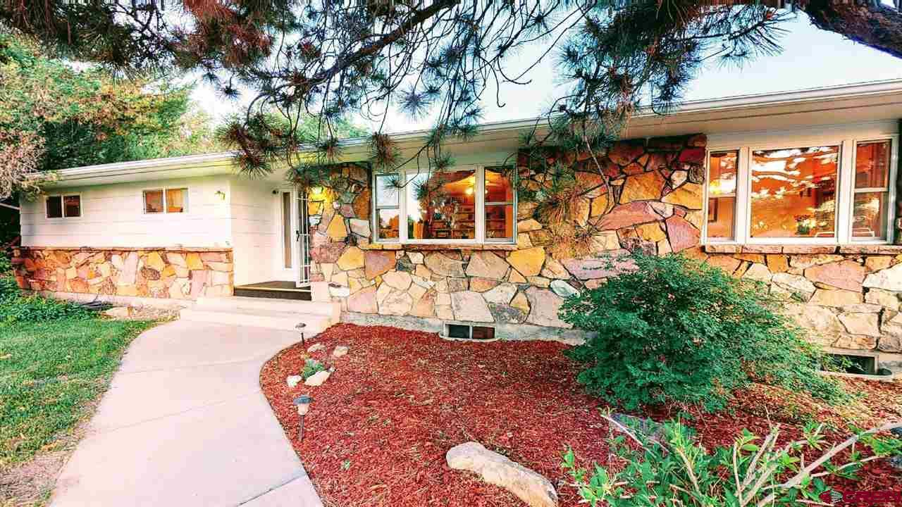 BEAUTIFUL, ELEGANT & SPACIOUS RANCH HOME ON 1 ACRE LOT WITH MOUNTAIN VIEWS! This Beautiful & Elegant Spacious Ranch Home is located on 1+ Acre Lot on Garnet Mesa at the Edge of Town, where the Town meets the Country! Its the Best of Both Worlds with a Peaceful Country Setting, yet close to All the Amenities of Town! The Attractive & Upgraded Ranch Style Home with Colorful Exterior Stone Accents boasts 4 Bedrooms, 3 Baths and a Full Basement. The Main Level includes the Master Bedroom w/Beautifully Tiled Master Bath, Granite Vanity Sink & 2 Closets. This Level also includes 2 Guest Bedrooms and a Beautifully Upgraded Tiled Guest Bath w/Laundry. Also on the Main Level is the Formal Living Room & Dining Room, but Best of All, is the Newly Upgraded Kitchen that flows into the Large Family Room with a Stone Fireplace. The Kitchen has all New Oak Cupboards with Slide-Outs, New Counters, Tiled Backsplash, Custom Built Utensil Drawers, a Built-In Desk Area, a Wide Eating Bar/Work Counter, Tiled Floors and a Pantry Closet - in short, this is a Dream Kitchen with Functionality & Beauty in mind! In the Mostly Finished Basement Level is the 4th Bedroom (non-conforming), yet another Large Family Room, an Office Area & a Large Storage Room for Canned Goods & other things. One of the Great Things about this Home is the Tremendous amount of Storage, such as Tons of Closets, Tons of Cupboards & Built-in Cabinets and Shelves. As you go into the Attached Garage, it also offers lots of Storage, Cabinets & Work Areas, then attached to that is a Carport. Along the Back of the Home is a Lovely Covered Patio (the Gas Grill is included & there's even a hook-up for a Hot Tub!), Large Landscaped Yard, a Very Well-Built Oversized Storage Building and a Dog Run. Last, but not least, is the Wonderful Mountain Views all around you! This Home, Setting & Location offer you the Comfort, Beauty & Space, Inside & Out, that everyone would LOVE to have! Note: The Freezer & Culligan Water Softener in the Basement has also been added as an inclusions.