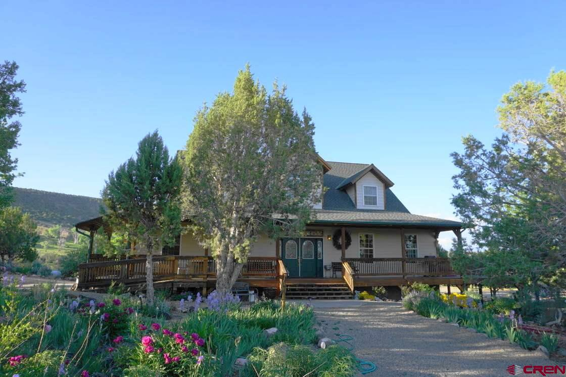 A lovely home and perfect hobby farm on Rogers Mesa! Backing into the beautiful Leroux Creek valley, the secluded property offers outstanding mountain views and consists of irrigated hay fields, an old apple orchard and pinyon-juniper forest. The 4BR/4BA home features extensive landscaping, a 3-sided wraparound deck and a living room with cathedral ceiling and spectacular windows. Main level master and 3 more bedrooms upstairs. Stay cozy with hot water in-floor heat and a two-sided wood burning fireplace. Quality construction includes 6-panel wood doors and wood windows. A walk-out/daylight basement includes an office, large family room, two other rooms that could be bedrooms and 2-car garage. Find yet more room for your cars and projects in the heated, detached 3-car garage/shop. There is also a large dog pen. Irrigation includes ample early and late water. An older conservation easement is on the property; it does allow the buyer to build a small second home and a second water tap makes this possible.