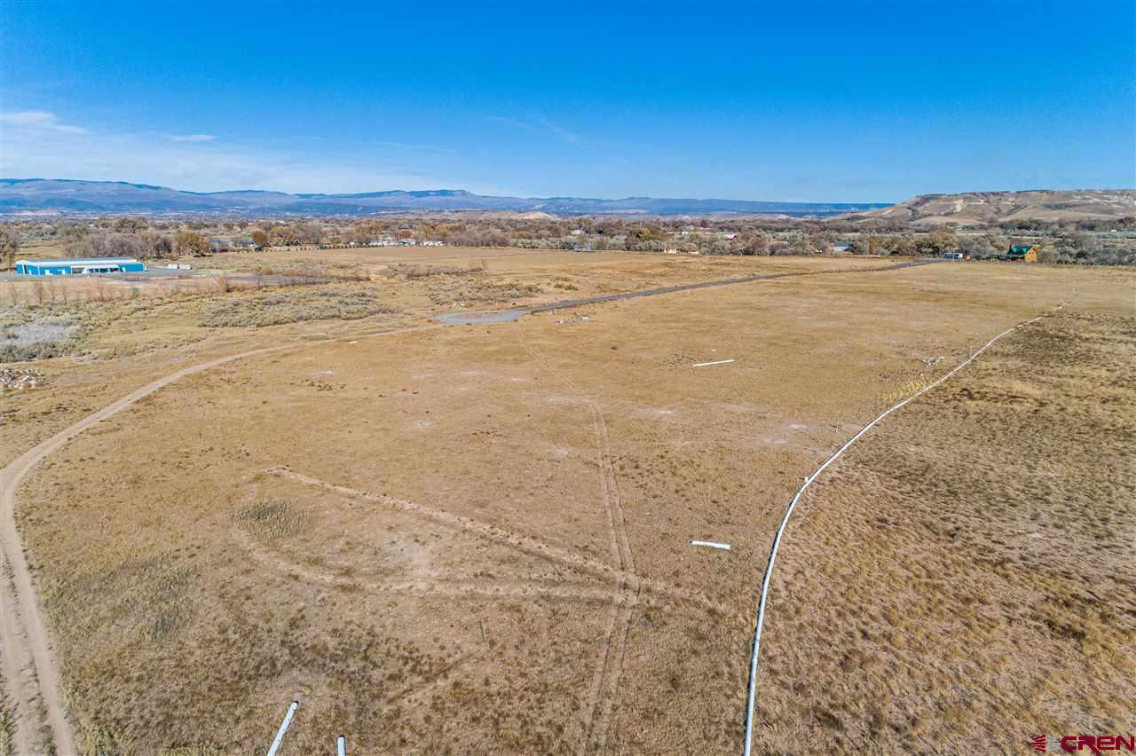 Excellent views from this hilltop location overlooking Tongue Creek Valley and the Grand Mesa! Great location for a subdivision, or growing a smaller crop with 55.9 shares of water, that include the Hal and Stillwater ditches. Electric close by. Entrance on Running Deer Road.