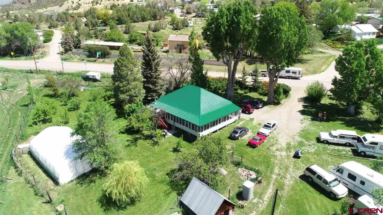"A must see, this property is a 1.71-acre oasis on Colorado's Western Slope, minutes away from the beautiful West Elk Wilderness and Gunnison National Forest. Zoned as residential and commercial, here is your opportunity for a new business or perhaps expanding the business that is already established, known as ""Peaches RV and Campsites"" that has two existing RV sites (50/30/110 amp) with electrical and water in place and are usually booked through the summer. Potential for additional RV spots. 2 water taps and 2 shares of Clipper Ditch, you'll never have to worry about irrigation for your lush yard which includes a massive hedge of gorgeous Austrian roses, 100 year old cottonwood trees and a small orchard of 25 fruit trees including pear, cherry, apricot, apple, peach, Italian plum, red plum and Canadian choke cherry completely surrounded by a 6' deer fence. Those who like to garden will enjoy the Weatherport 20'x40' greenhouse filled with premium soil and raised beds.  Home features 2 bedrooms, 1 bath, large living/dining room, built-in book shelves, ceiling fan and appliances. New floors and drywall were installed in 2003. Home is heated by natural gas keeping you toasty warm in the winter for an average of $75 even in the coldest months. Enjoy expansive valley views from the enclosed, screened-in porch that wraps around two sides of the house with a heated sunroom and wood stove to keep the chill off on those cool nights. On the back half of the property there is a 25'x35' wooden barn with a loft. The Central Irrigation Ditch runs through this portion of the property. Property has a second paid water tap that for an additional fee, can be considered a COMMERCIAL water tap as well as a second paid sewer tap. Riding lawnmower included. New pump has been recently installed on the irrigation system. Metal roof installed two years ago and has lifetime warranty. Bring your touches to the shabby-chic, eclectic old wooden 2nd shed that could be made in to an outdoor living area with a bed in the loft or a cabin. Walking distance to downtown Crawford, restaurants, library and more. Crawford Reservoir is one mile away with world-class fishing, boating and camping. Black Canyon of the Gunnison National Park is within a 20-minute drive and is spectacular!"