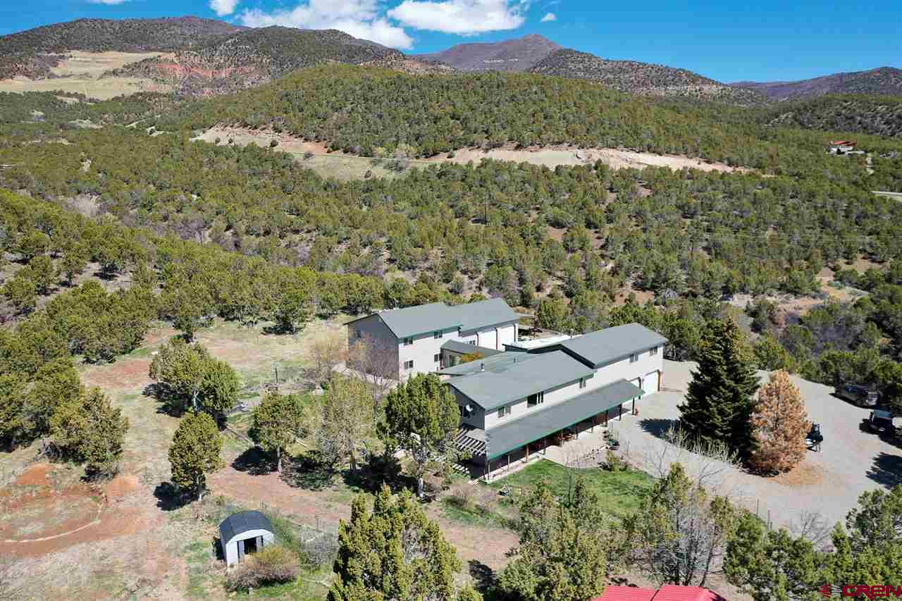 Location! Location! Location! Stellar views of the West Elks from this beautiful property that backs to BLM on one side and a canyon on the other. It's close to Paonia, but private and secluded at the top of a quiet cul-de-sac. The home is perfect for a combined family situation with a main house in front connected by a breezeway to a 3BR guest wing addition in back. The main house features 2 master bedrooms, multiple living areas and an attached 2-car garage. Recent kitchen updates include fabulous new granite counters, alder cabinets, 2 sinks, double ovens, smooth-top range and an oversized island. The guest wing was added in 1997 and is mostly complete and highly livable despite a few unfinished details. It comes with 3 bedrooms, 1 finished bath (with laundry area) and 1 roughed-in bath, plus kitchen and attached 2-car garage. The exterior is landscaped with rear yard sprinklers, deck, patio and RV parking, plus established strawberries, raspberries and plums.