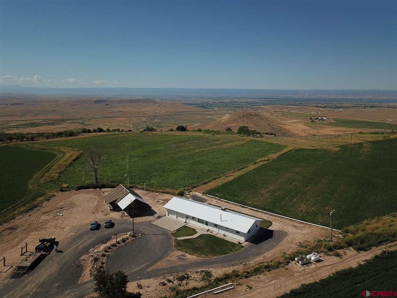 Redlands Mesa ranch with captivating 360 degree views! The end of the road location offers seclusion, privacy and quietness. Approximately 35 irrigated acres with incredible versatility for a variety of crops with ready to go irrigation system in place. Currently a productive hay/alfalfa field with a farm lease that could be continued or terminated. Diverse terrain of the property ranges from flat irrigable ground to sloping with a brush/tree area, making an exciting wildlife opportunity. After a good days work, retreat home to a 3 BD/2.5 BA low maintenance home that was intentionally designed to enjoy the incredible views. Metal roof, over insulated home and two car attached garage. A full unfinished basement makes a wonderful shop or storage room. The NW parcel corner touches BLM. Property is surrounded by other large parcels.