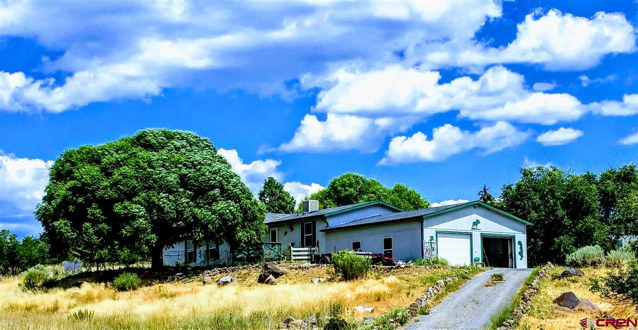 Country Living & Incredible Views at an Affordable Price Tag! Enjoy the Country Life in a Peaceful Setting with Privacy in this Lovely 2003 3-Bedroom, 3 Bath 2016 Sq.Foot Manufactured Home on 1.25 Acres, and Imagine Sitting on Your Deck Enjoying the Fantastic Views this Property has to Offer. Lots of Custom Features in this Home and a Well-Built Attached 2-Car Garage that the Owner added with 2 Separate Roomy Storage Rooms in the Garage with one of them being a Cool Storage Room. There is an Enclosed Sun Porch, a Spacious Family Room in Addition to the Living Room with Impressive Design Vaulted Ceiling & Lots of Windows for Light. There's a Wonderful Large Kitchen with a Work Island, Separate Pantry Closet and Tons of Beautiful Cabinets. There are 2 Full Baths and a ¾ Bath, making a total of 3 Bathrooms. The 2x6 Walls are well insulated, and there are Extra Electrical Panels installed on the outside. Includes 3 Additional Nice Storage Sheds and Multiple Fruit Trees – 2 Apple, 2 Peach, 2 Bing Cherry, 1 Pie Cherry and 1 Apricot. There is an Additional Refrigerator and a Freezer that's also included.