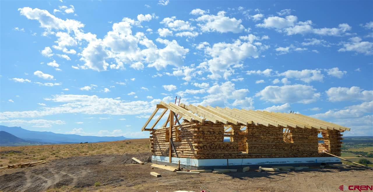35 acres of wide open spaces and superb mountain views. Seller is building a 30'x50' log cabin shell. Designed for a 3 bedroom 2 bathroom home, but could be made into anything you want. No septic, doors or windows included. Excellent views of the West Elk Mountains, The Ragged Mountains, Black Mesa, The Grand Mesa, and the North Fork Valley below. This is one of the furthest parcels clear up on the ridge to the south with edge of the mesa building sites looking off to the south over Grandview Mesa, and with complete 360 views. No Covenants. BLM Public Land is near by. Electricity, water line, and Elevate Fiber conduit line (not available yet) are all to the property (along Sagebrush Rd). Includes 1 Indoor Water Tap, and 2 Outdoor taps for irrigation and/or livestock water. Plenty of room to roam and you'll never tire of the views! (Photos of the home are of the home built by Seller on the neighboring property. The home being built will be similar).