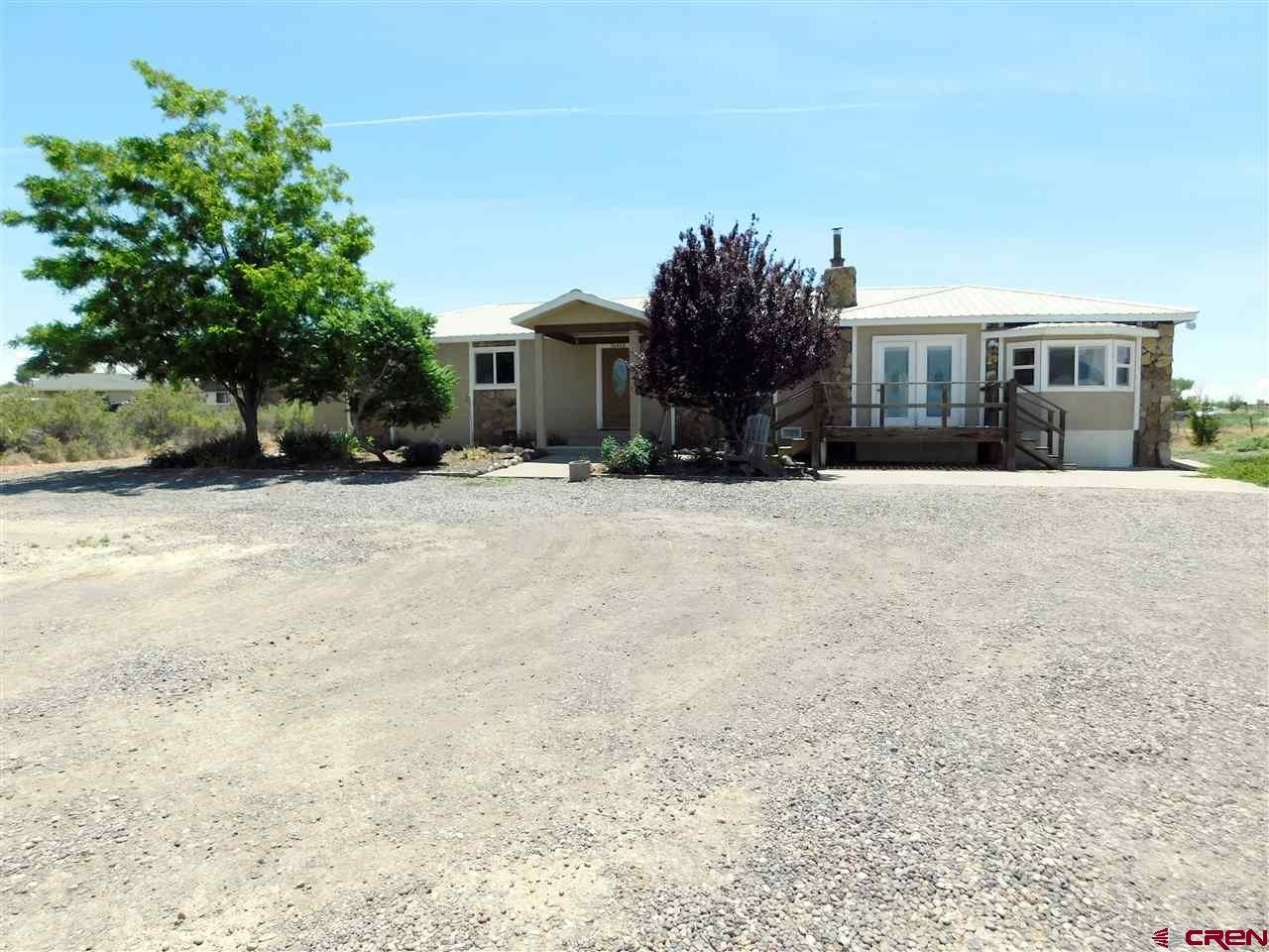 Stucco and rock sided home on 1.5 acres with nice views of the Grand Mesa. Large covered back patio, metal roof, partially fenced and landscaped. Fantastic oversized 2 car detached garage with workshop area. Cozy fireplace accents the living room. Large kitchen with sliding glass doors to covered patio. This home offers two master suites on each side of the house. The 3/4 bathroom has been recently remodeled with tiled shower and flooring. The second master area has large picture windows, private deck, sitting area, large walk in closet and five piece master bathroom. Tankless gas hot water heater keeps the hot water flowing for the whole household. Located within easy driving distance to Delta or Cedaredge.