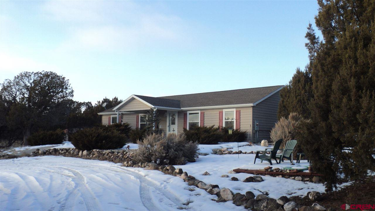 """Enjoy the quiet and outstanding views from your covered front porch or covered patio of your home on 30 acres just 6 miles from Cedaredge.  On the edge of Cedar Mesa, this location is convenient to either Cedaredge or Hotchkiss and not far from Delta.  This home, built in 2006, features three bedrooms, a den and a great room with vaulted ceiling is perfect for entertaining or just enjoying the open feeling of being able to see all around.  The 15 by 39 foot covered patio in back has been built so that it could become part of the home, if desired.  There is also a gigantic detached garage/shop that is insulated and finished with particle board.  A big work bench is built on one side, and there is an enclosed room for the compressor and equipment.  220 service and plenty of electrical outlets make this space just right for all your projects, hobbies or just convenience.  The property is partially wooded with cedars and pinons, and although there is no irrigation water for the property, two seasonal irrigation ditches cross the property providing live water for ambience.  Come enjoy being in the country with lots of """"room to roam."""""""