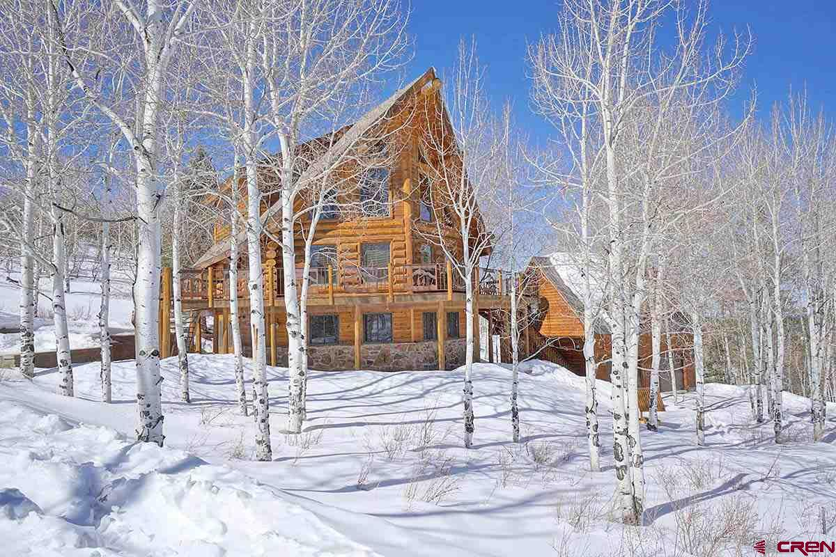 Quiet, private and protected, this picturesque Colorado Mountain Log Home is nestled among Aspens at the foot of the beautiful San Juan Mountains. At 8800 feet, this home in Elk Meadows subdivision offers maximized views of the inspiring Cimarron Mountain range known for its sunset Alpen Glo. And it's only 20 minutes from Ridgway.   A local log home builder from Montrose built this house from white pine logs. The open Great Room on the main level offers soaring wood ceilings, beautiful log timbers, lots of natural light and spectacular views. The open kitchen has beautiful knotty pecan cabinets and 2 year old stainless appliances. A gorgeous deck wraps around on three sides of the house. Be sure to notice the custom metal railings.   Each of the bedrooms in the home is on a different level. There is a guest room on the main level and full bath.    The master bedroom on the upper level has sweeping mountain views. The adjoining master bath has a jetted tub as well as a shower and a large walk in closet.    A second guest room in the garden level basement has a full bath and laundry as well as a living room with a pellet stove.   Only steps away is a detached oversized 2 car garage with a beautifully finished 550 sf flex space that could have a number of uses.  Elk Meadows is a high country subdivision with its own solar powered water and sewer system.