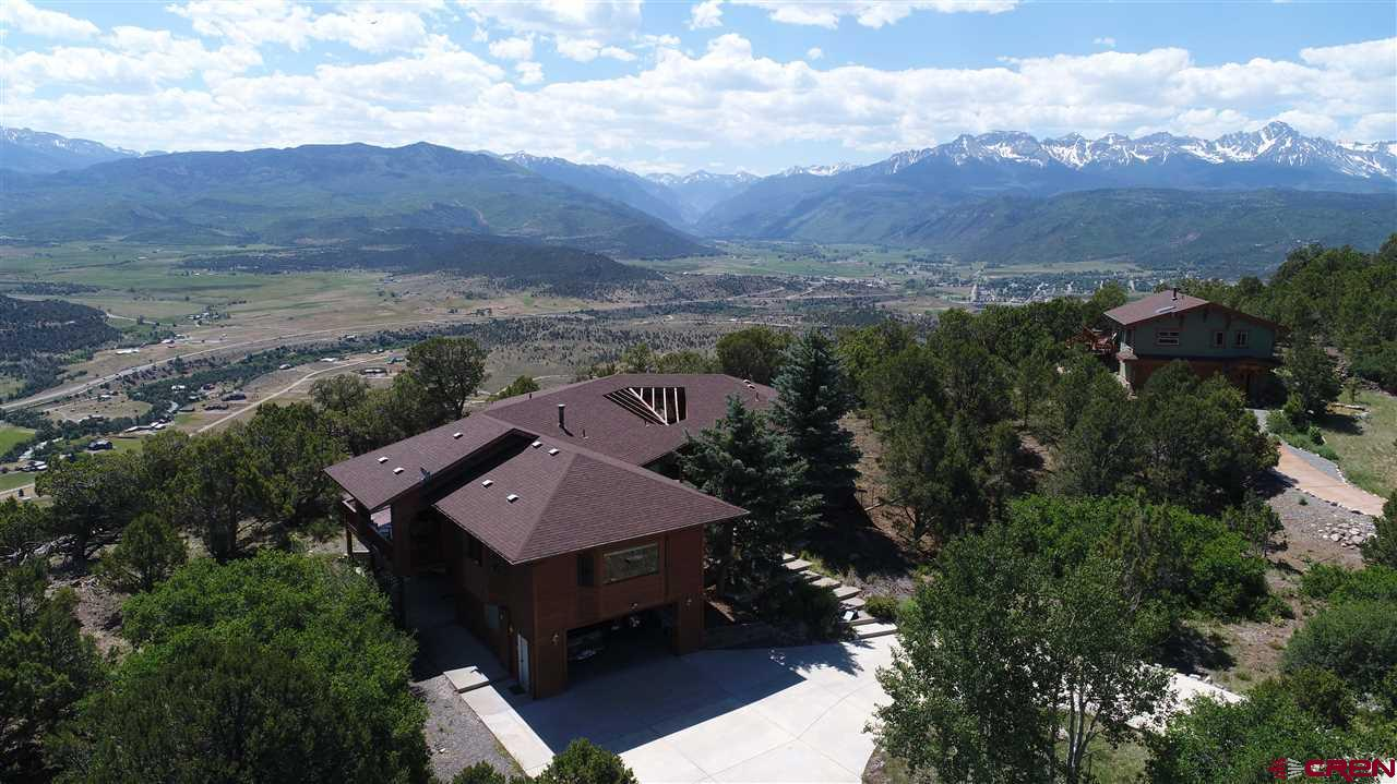 STUNNING home with panoramic views of the San Juan Mountains, Cimarron Mountains, Ouray Valley and the Northern Mesas.  Very rare find to have 5.12 acres on the escarpment.  The property is being sold with an additional vacant lot, adding to the privacy and serenity. The surrounding home sites, have already been built upon, therefore the views and privacy will not be obstructed. This gorgeous home has unbelievable views from the massive windows and covered wrap around deck leaving you breathless. The upstairs main level has an open floor plan with kitchen and living. The kitchen is spacious and open, with a large breakfast nook for meal times. The living room offers a warm comfortable setting for home owners and guests alike.  Views are available from all rooms on the main level.  The master is set off to one side for privacy.  The main level consists of:  master bedroom, master bath, guest suite with own bath, guest bath, office, living room, kitchen, and family room.  Lower level consists of:  2 bedrooms, one full bath, full kitchen, gym area and huge storage space.  The concrete wrap around circular drive supplies guest parking along with a 2 car attached garage for owners. The flooring consists of:  gorgeous hardwood, tile and partial carpet.  The heat is the very efficient natural gas-hot water baseboard.  The downstairs could be a separate living quarters since it does have a bathroom with steam shower and kitchen. This is a rare find, come take a look and make it yours today!