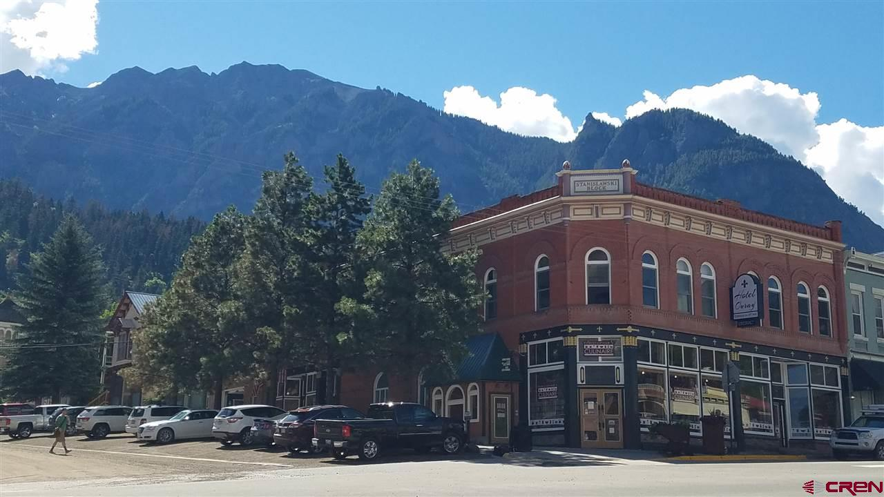 """Once in a lifetime turn-key opportunity!!! You will find this hotel in charming and historic Ouray – also known as """"Little Switzerland of America."""" This one of a kind boutique hotel offers additional retail rental spaces as well.  Built in the heyday of the mining boom in 1893 and right in the middle of town, it gives you walking distance to all the restaurants, shops and amenities of Ouray.  Complete renovation and remodel done in 1993 to assure the building was in compliance with the current building and safety codes.  The last five years have seen cosmetic and logistical upgrades throughout.   Updated bedding, mattresses, towels, down pillows, lamps, light fixtures as well as internet and phone system.  The unique antique furniture has been restored to its original beauty.  The entire second floor hotel has new carpet as of November, 2019.  The lobby area is custom built so that the front desk matches the historic staircase and gives you continuity of décor throughout. This impressive building includes three retail units on the street level, one retail unit in basement with separate, covered stair entrance, on corner of 6th and Main and one additional small retail space, in back of lobby, on street level for a total of 5 units in addition to the 14 room boutique hotel on the second floor.  All of the comfy 14 hotel rooms have a private bathroom which has been beautifully renovated complete with heated tile floors. Retail spaces are all currently occupied with existing leases in place.  This will be your dream job/business.  The charming and historic boutique hotel brings the guests back year after year.  You grab up this deal and just take over the existing systems and business in place – which includes the impressive website - and settle in to this amazing community.  It's a beautiful place to call home and such a promising opportunity - must be seen to believe!"""