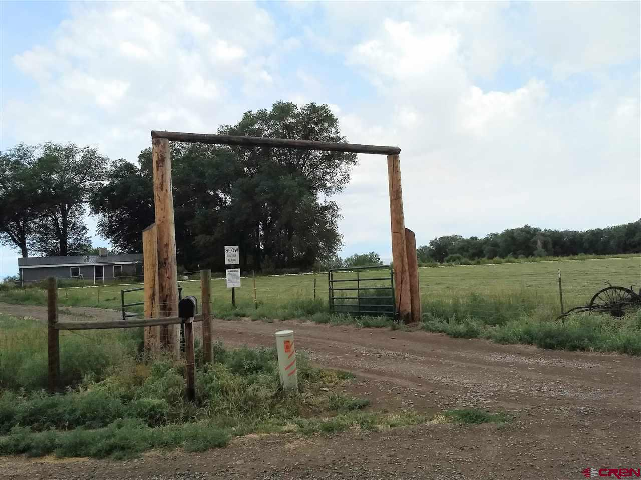 40 acres -22.5 shares UVWA irrigation water -1988 Titan double-wide mobile home. 3/2 with approx 1400 Sqft. (26X56) -30X40 square steel garage with full foam insulation, double doors both ends, concrete floor, full electric, parts room, and upper level office and storage area. -40x40 steel quonset hut with concrete floor, full electric, and double doors. -Property fenced on all 4 sides. Septic recently pumped - 1250 gallon tank -service receipt available. -One half mineral right included... -Approx 22 acres farmable area, with remainder hilly pasture/marshy area. -Includes small pond -Wonderful views of Grand Mesa, Mount Lamborn, and Delta and Uncompagre valley and mountains.