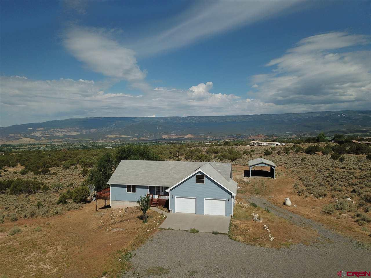 Fantastic Grand Mesa views from Cedar Mesa! Lots of room inside and outside; and ready to move i! Fresh exterior paint! 9.72 acres, no HOA. Two car attached garage plus RV/Boat shelter. This home features an attractive open floor plan with 1386 sq. ft on the main level, including the master bedroom. Upstairs office or hobby room offers 360 sq ft and the finished walk out basement completes the living space with a huge family room, bedroom, bathroom, storage and more. Clean, comfortable and ready to go! This property could possibly be subdivided. Come take a look!