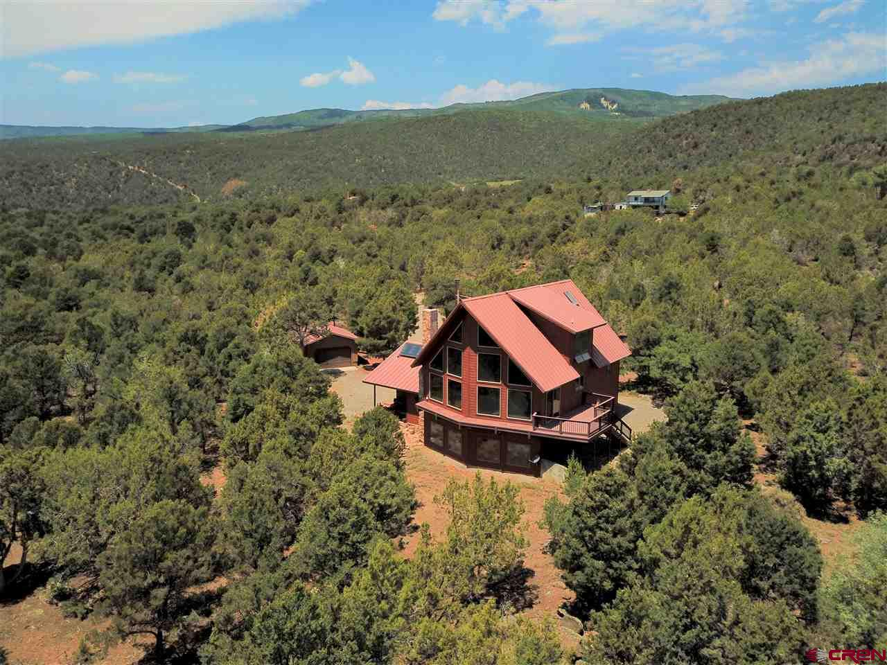 Western Colorado mountain home, privately tucked away in the trees with inspiring views. Located at the end of a private driveway, this peaceful home is sitting on 8.46 treed acres at an approximate elevation of 6,840 feet. This three level home is wrapped in cedar siding (recently stained), has a metal roof, an East facing deck and private upper level balcony. A new wood stove in the living room creates a perfect environment to enjoy the outdoors. Gorgeous wood floors and tongue-n-groove ceiling. All the light bulbs have been changed to LED lights keeping the electric bill low. A central vacuum system as well! When you enter the home, you will be greeted by the beautiful foyer, sun room with great passive solar heat. One bedroom, bathroom, laundry room and workout room or workshop. Walk up the stairs to the large living room, kitchen, two more bedrooms and full bathroom. Take the spiral staircase to your own sanctuary featuring a sitting room, huge bedroom, bathroom and balcony. Views, views, views from everywhere! Two car attached garage plus two additional detached single car garages and workshop. Walk down the trail to enjoy the live water flowing through the seasonal ditch. There is also a small root cellar. No HOA. No Covenants. So many wonderful things to enjoy and explore on this property, all perfectly situated close to the Grand Mesa.