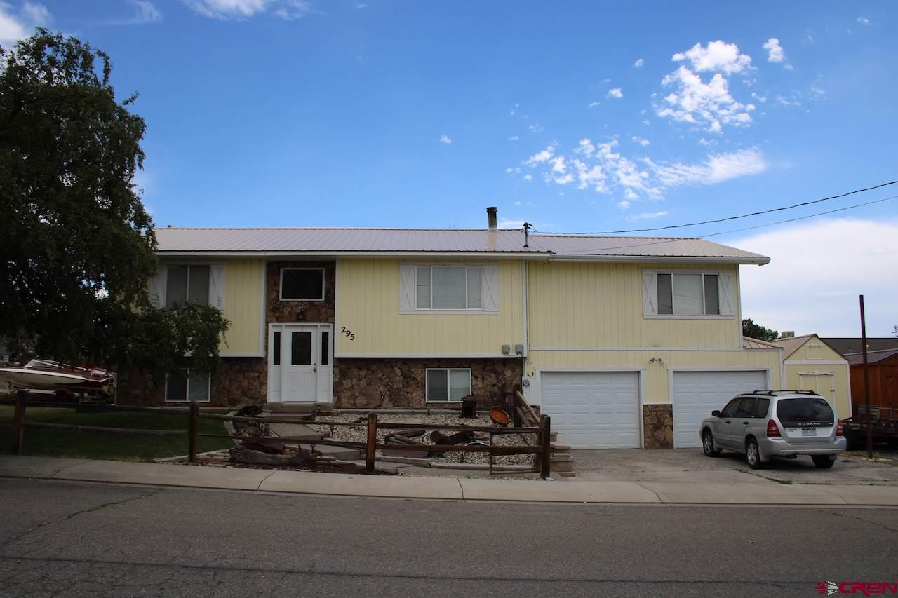 Hard to find this much square footage for the price!  This spacious 2,628 +- SF home features, 4/BR, 3/BA, Bi-Level with the Master Bedroom and Main living area upstairs.  Extra large 19'9 x 27' living room with built in bar, perfect for entertaining.  Open concept living with eat-in Kitchen bar, separate dining area with vaulted ceilings.  Free standing wood stove provides plenty of heat for the entire home.  15' x 27' master suite on the main level with full master bath.  Large corner lot with privacy fenced back yard and enough space for RV parking with electrical hookup.   Covered back deck, outdoor storage shed, mature landscaping and a great area for a garden.  Close to downtown Cedaredge in a very desirable, quiet neighborhood.  This home has been renovated with several upgraded appliances including the water heater.  Call for a showing appointment today!