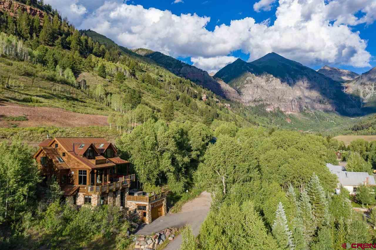 Perched on the hillside of a quiet, sunny street, this expansive custom cedar and stone home has the best views in the Town of Telluride. The multilevel floor plan includes private bedroom escapes, offices with inspiring views and a sunny artist's studio. The main level's open design offers grand spaces for entertaining with coffered ceilings, fir timbers and fine craftsman details complementing giant windows showcasing unobstructed views of Bear Creek. Spacious decks off multiple levels feature unbeatable views spanning Ajax to the ski area to striking sunset vistas. Amenities include easy access to trails, double garage with built-in workspaces and hot tub with stunning views. A short walk from main street, protected views and privacy make this one of the finest homes available today.