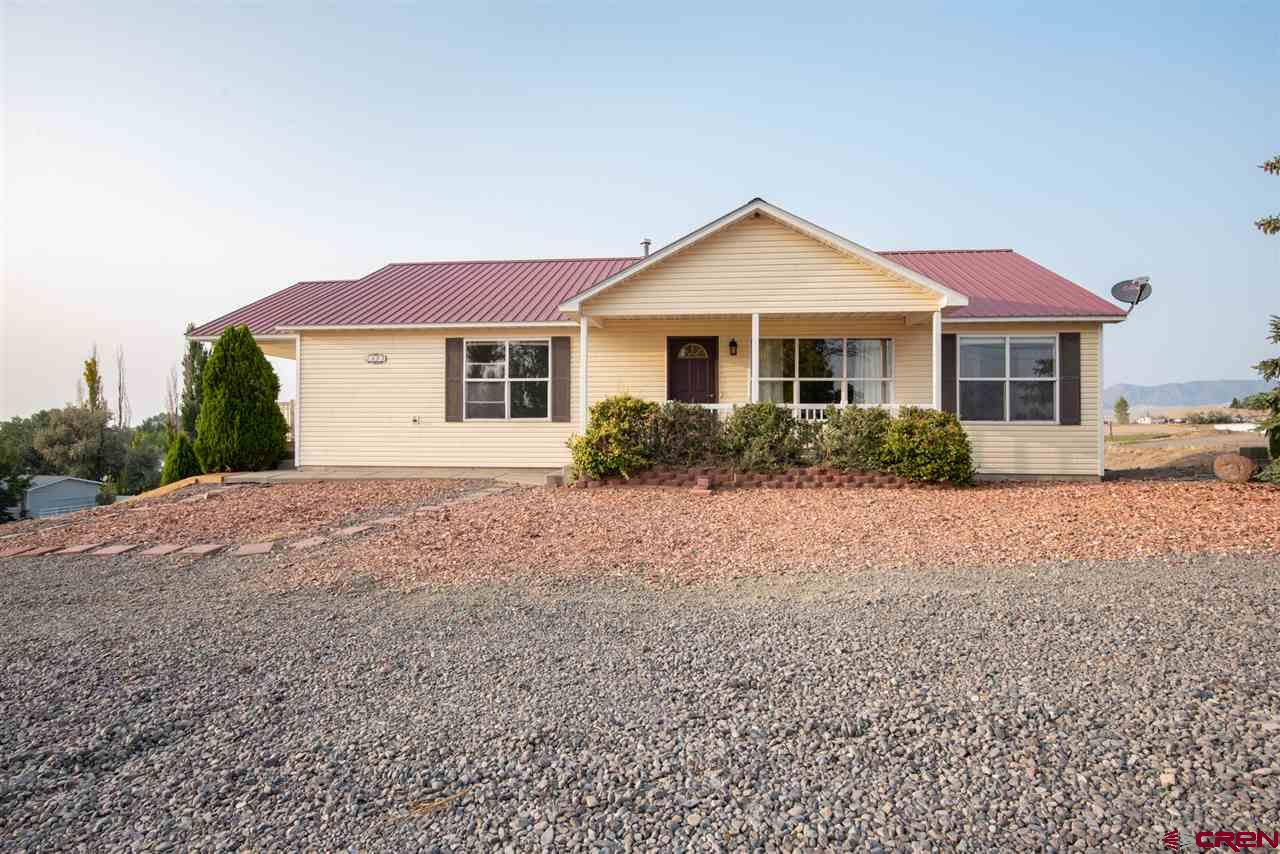 This wonderful ranch style home with walk out basement is located on 3 irrigated acres just outside city limits with no HOA or covenants. On the main floor you'll find a spacious open-concept living room, dining area, kitchen and breakfast nook. You have a great view of the southern mountains from the covered front patio and living room, and from the dining area you can access a deck to enjoy the views to the north. The kitchen has ample cabinet and countertop space along with a butcher block island for prep work. There is an additional breakfast/dining area off the kitchen where you can access a very large covered deck and, YES...more views. This is an amazing place to watch the storms roll in, the sun set, and the city lights! The master suite, 2 additional bedrooms and a full guest bathroom are also on the main floor with a split floor plan. Located in the walk out basement you will find a 3/4 bathroom and 2 large semi-separated rooms that could be used as a bedroom or additional living space. From this level you can also access the 2 car garage. The front of the house is xeriscaped for minimal yard work. The back acre or so is currently in grass/hay and taken care of by a local farmer and can stay that way if you'd like, or you can fence it off to use as you need. Home does have a shared access entrance off Locust Road.