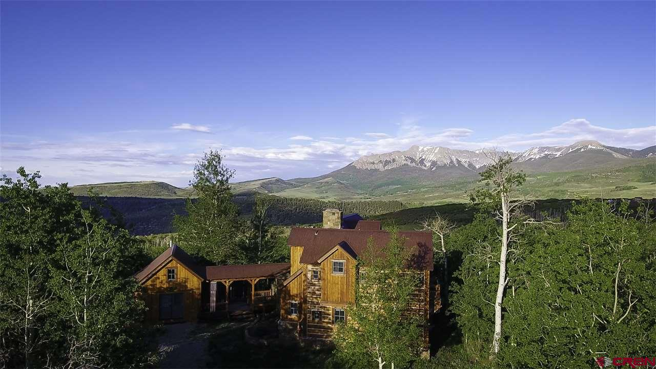 ''Mountain Sky'' is a glass, stone and timber cabin at 9,100 ft elevation on Hastings Mesa just 25 min from Telluride. A new trail system graces the 54 gently sloping acres with a beautiful mix of mature trees. Through the 2 story windows, you'll have views of the ever-changing sky, Uncompahrgre Wilderness & Sneffels Range. Vibrant summer colors, bright green aspen forests & bluebird skies... the odd cloudy or rainy periods where the clouds race across the sky, white snowy winters to enjoy the hot tub. Three bedrooms/two baths in the main house, as well as a large finished open plan lower level, separate finished workshop accessed by a breezeway with a bath/shower, and a detached new 2.5 car garage with second floor storage.  Many upgrades since the current owners purchased, including new detached oversized 2 car garage with 2nd fl storage; finished workshop with bath / shower; new well, cisterns, boiler; new hot tub, radon mitigation system and new trail system throughout property. The home has been totally sandblasted, logs power brushed, re-stained and re-chinked. Exterior stairs have been replaced and metal siding added to decks. Owner has an established AirBnB site that can be assigned to new owner.