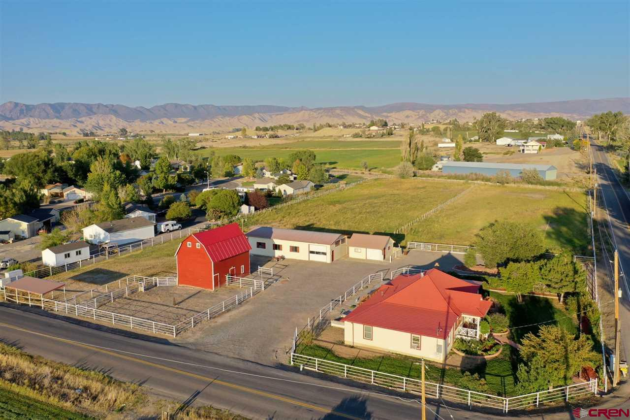 PRICE REDUCED! Don't miss this renovated farmhouse situated on 4 acres with irrigation water, outbuildings and views! The home, originally built in 1914, has been beautifully restored to offer the comforts of modern living while maintaining the integrity and charm of a home from the early 1900s. There is room to spread out with 4 bedrooms, 2 bathrooms and plenty of porch space to take in the 360? surrounding views. One of the bedrooms could make the ideal home office with a separate entrance, private porch, and magnificent San Juan Mountain views.  The home underwent a permitted addition in 2015-16 adding 2 large bedrooms, remodeling bathrooms and updating the rest of the home cosmetically with new hardwood flooring in addition to bringing the home up to code. Feel secure in the basics with a new electric panel, newer roof, windows, a new 45-gallon hot water heater and updated insulation throughout the home for energy efficiency. Outside you'll step into a yard that offers all the charm with mature landscaping, fruit trees, grape vines and an automatic sprinkler system. The property beyond includes a circular drive offering a convenient turnaround for RVs, trailers, and more. You will also find a detached garage as well as a 36'x70' shop with concrete flooring. The shop leads to a smaller workshop with floor drain and various horse stalls. The property also boasts a functional restored historic 24'x32' barn with new paint and a new roof and a stunning cathedral loft. Horse enthusiasts and hobby farmers will adore this property with multiple pastures, stalls and corrals surrounded with sturdy white pipe fencing. The large pasture is currently irrigated by sprinkler gun system, but can also be watered with included gated pipe. The property is irrigated with 2 shares of water allocated through UVUWA for $250/year. No HOA! Don't miss your chance at this one!