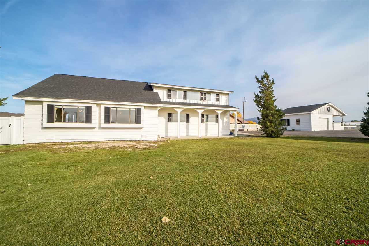 Welcome home to one of Montrose's most distinctive properties. This home is truly one of a kind. It has the a country feel and lifestyle with its 3.45 irrigated acres of lush green grass and beautiful park like setting where you have the freedom to raise 4-H animals, create your own hobby farm or just sit back and admire the breathtaking views of the San Juan Mountain Range, all while enjoying the benefits of being close to town and situated in an upscale residential area. On the South end of the property sits a 30x50 Shop with 220 electric, a wood pellet stove and a composting toilet. Between the home and the shop there is an additional detached garage with attached carport.  The quaint farmhouse has so many desirable features. When you open the front door, you are greeted with the warm, natural light filtering in the big picture windows. You immediately feel at home with the open concept kitchen, dining and living room, accented by the wooden beams and vaulted ceilings. Beyond the kitchen is the main bathroom with a soaker tub and stall shower. Followed by the laundry room and bonus room, which is currently being used as a home classroom. Then the one car attached garage with tons of additional storage. Upstairs you will find three bedrooms, one full bath, a reading nook and a spacious and open loft area currently being used as the master bedroom.  This property is perfect the way it is, but maybe you are looking for other opportunities. This property offers rare and highly desirable development options as current owners presently have approval from the City of Montrose to subdivide or build an additional home on the property with or without annexation into city limits. Do not miss out on your chance to own this iconic Montrose property that  is a local favorite. Schedule your private viewing today!  Professional pictures and video drone are coming soon, so check back!