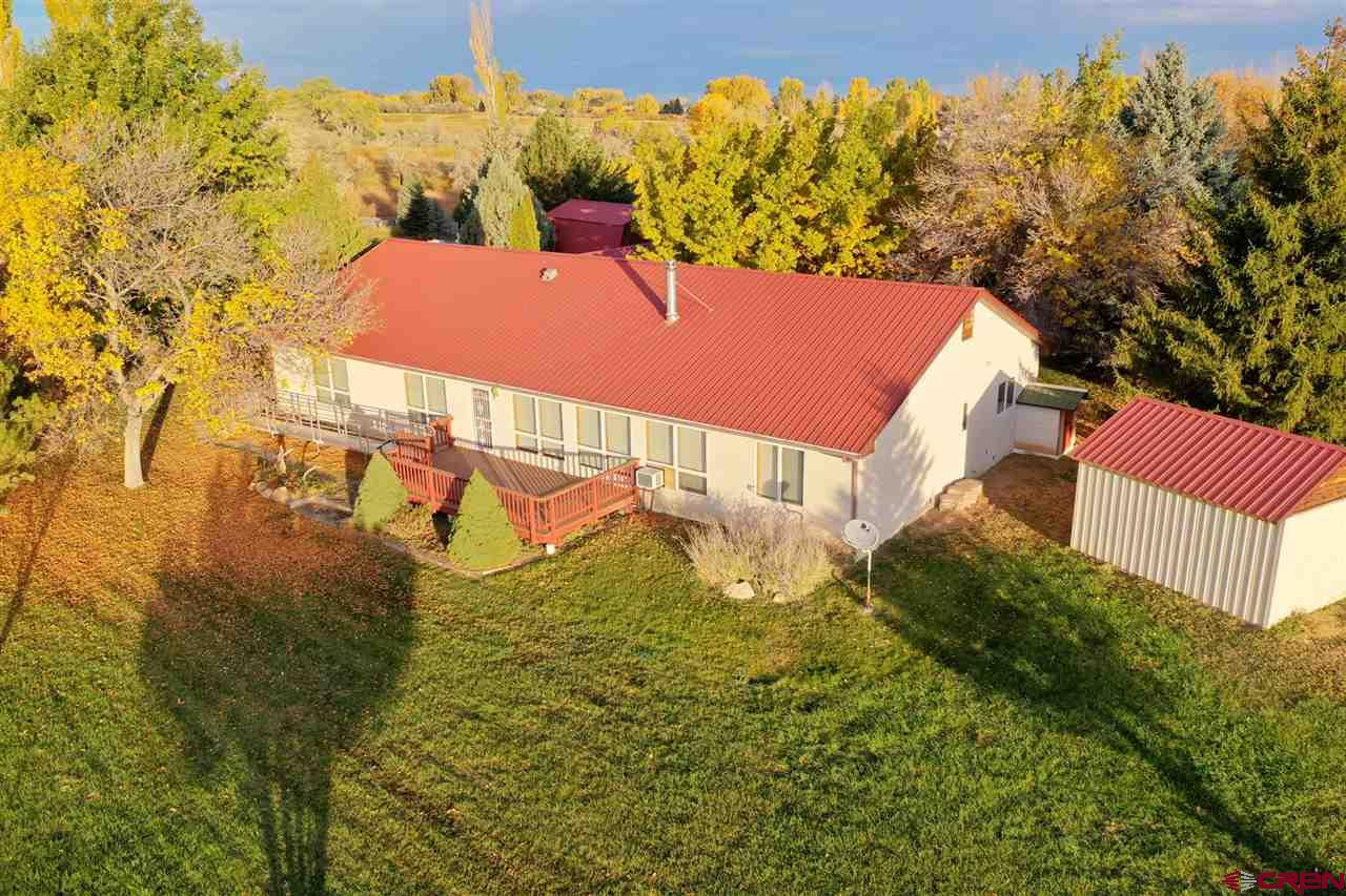 Fantastic Spring Creek location!  Nestled off a paved road and surrounded by mature trees, this peaceful setting is just minutes from town.  The ranch style home on 4.23 beautiful acres is situated to overlook pasture, rolling hills and the mountains view beyond.  This one owner home was designed to take advantage of Colorado's average 300+ days of sun and the benefits of passive solar with an abundance of natural light in the living area provided from southern-facing windows, warming the Saltillo tile.  Additional warmth in the winter months is provided by the living room woodstove.  Impeccably maintained red oak floors span the living room and two of the three bedrooms.  The country kitchen is open to the living and is separated to the dining area by a kitchen bar.  Cabinetry in kitchen includes roll-out drawers and a pantry provides added storage.  An interior brick wall in the dining area provides more warmth to the space.  The main level master bedroom has a vaulted ceiling of aspen wood, a ceiling fan, walk-in closet, and spacious master bath with walk-in tub.  The third bedroom has Saltillo tile, two closets and can be entered from either the living area or main hallway.  Turn the flex room off the dining area and garage into a workout room, craft room or workshop.  Laundry room has extra cabinetry and a utility sink.  The oversized 2-car garage has electric baseboard heat on its own thermostat and the driveway outside is covered.  The remainder of the home has hot water baseboard heat, each room on its own thermostat.  Home also has a central vacuum system.  Outside is a 480sf deck, a spacious but easily maintained yard on a sprinkler system using irrigation water, a nice 448sf barn with cement floor, electricity and loft area, and an additional storage shed.