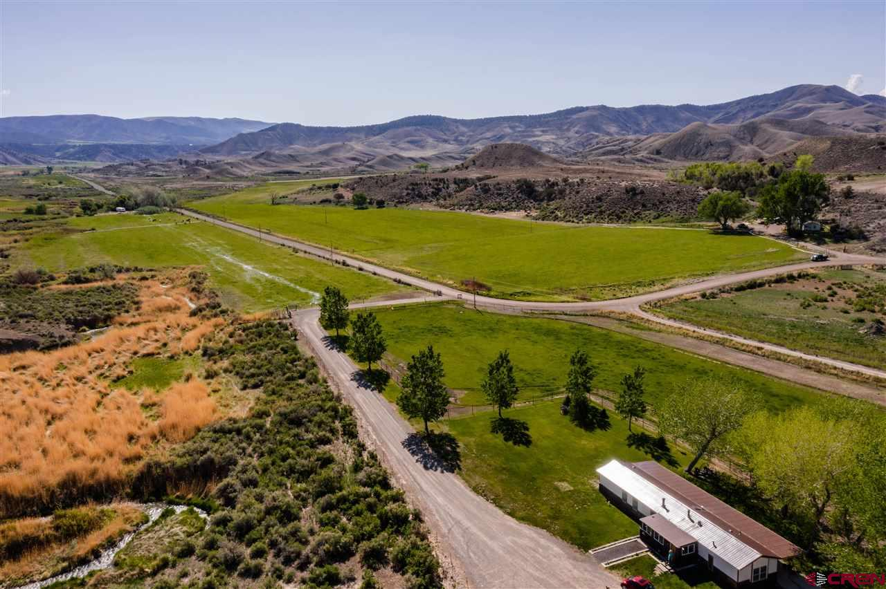 Located just outside of the charming mountain town of Montrose, Colorado is the Cedar Creek Ranch.  As convenient as they come, this 476± acre working cattle ranch, with its 133 irrigated acres, has produced ample amount of hay for generations of farmers in this valley. With winter-feeding ground of irrigated hay pastures scattered between dry ground and nearly 2 miles of river bottom, this valley ground makes for a perfect wintering ranch for livestock. Modest improvements consist of a 1,296 square foot farmhouse for a working rancher, multiple outbuildings, and cattle handling facilities conveniently located right off the road for easy access. Beyond the current residence atop the hill is a cluster of mature cotton woods, shading a small pond. This site is excellent for building a home site with gorgeous southern views to the San Juan Mountains. If you are needing a wintering facility to your high-country ranch, this one is a must-see!