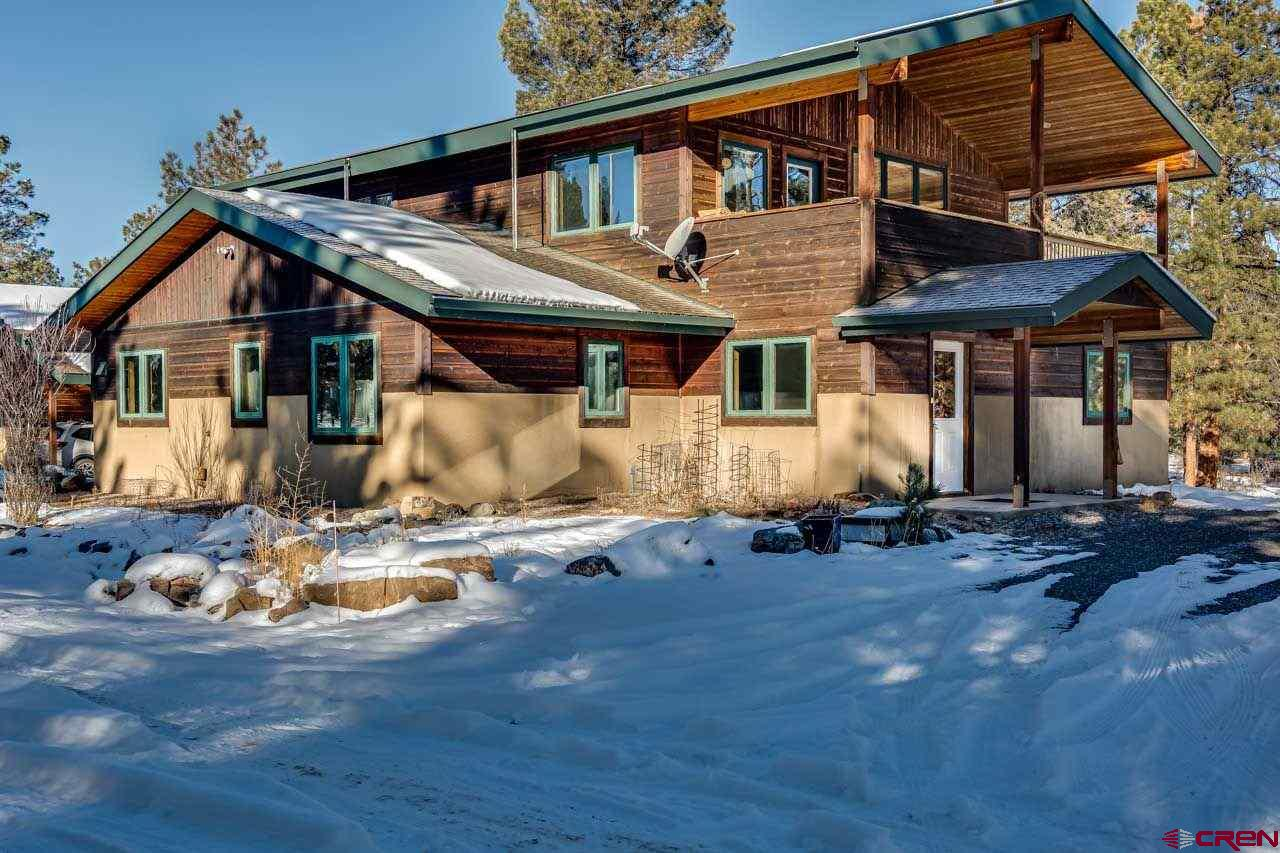 Set in a Ponderosa pine forest, for privacy, yet with very good views of the Cimarron Range. This 2 bedroom, 2 bath house is very comfortable, The exterior walls are Structural Insulated Panels (SIPs) for strength and energy efficiency; in-floor radiant heat and triple-glazed windows enhance comfort.  The house is designed with a large studio that could easily be a couple of bedrooms, family room, media room, a mother-in-law suite; or used as is. Along with the studio, the ground level has a large laundry room/mud room, large pantry and wine cellar, large office, a bedroom, and 3/4 bath.  The upper level has a delightful well arranged galley kitchen, living/dining room, master bedroom with walk-in closet, and bath; all surrounded with well placed large windows for great light and taking in the fabulous views.  The second level deck, off the dining room, affords outdoor meals with a view! Just steps from the house is a dream workshop that is approximately 1,800 sq. ft. of clear span space. The workshop has 2 large overhead doors, in floor heat, a wood burning stove, 1/2 bath, power and water. The workshop is also constructed with SIPs. It is currently being used as a garage and wood shop but could be put to other uses if desired. The workshop has very large shed-style wings for storage and/or carports the full length of the sides; almost another 1800 SF of covered space.  The quality of the custom woodwork in this home is unmatched in any currently available house the area
