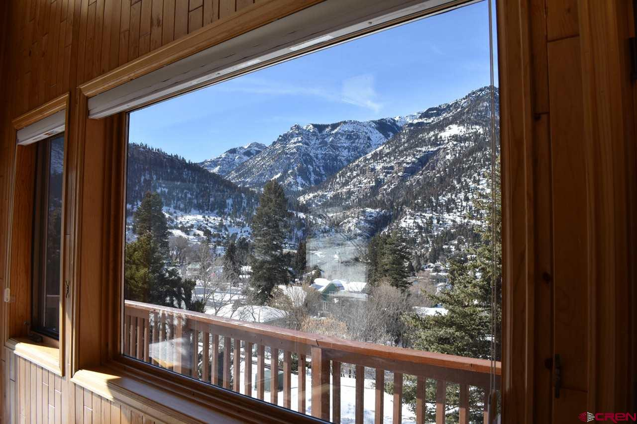"""Have you heard the old saying, """"Location location location""""? It refers to this place.  In Ouray you are surrounded by towering mountains.  Every direction there is a view.  This 2072 square foot home is located on almost the end of a dead end street where tourists don't go.  It also has 360 degree views and a 14,200 square foot lot. (Four - 25X142 city lots)  The house can be changed, the location can not.  This home has a nice two car attached garage and a large zero scape yard.  The exterior has stone and cedar siding.  The main level has a nice great room with a large kitchen, beautiful stone fireplace, two story windows, two bedrooms, a full bath and a large laundry room.  The upper floor has a master bedroom loft with a really nice walk in closet and master bath.  Walk to town, walk to the pool, hit the perimeter trail less than a block away.  This place is worth seeing."""