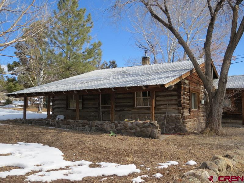 This is that log cabin in the country you have been looking for. The views to the south are fantastic. Actually there are nice views all around. This quaint home on 2.7 acres is away from it all, but still close enough for a quick trip to town. The home is rustic throughout, (but perfectly functional) and waiting for someone to give it a new look. It does need TLC. The back rooms aren't heated, but would make a great sunroom or a large second living room, or...use your imagination. These rooms would also be great for year round gardening if you add a heat source. Outside you have an oversized two car garage with a workbench. There is also a large room over the garage. Behind the garage is a large metal building that can be used for storing additional vehicles, campers, an RV or whatever you want. There is a lot of wildlife to enjoy including foxes, turkey, deer and the occasional bear. The deer love munching on the fruit from the wild apricot tree, and the two apple trees behind the house. A seasonal irrigation ditch runs through the back part of the property, but there aren't any water rights.