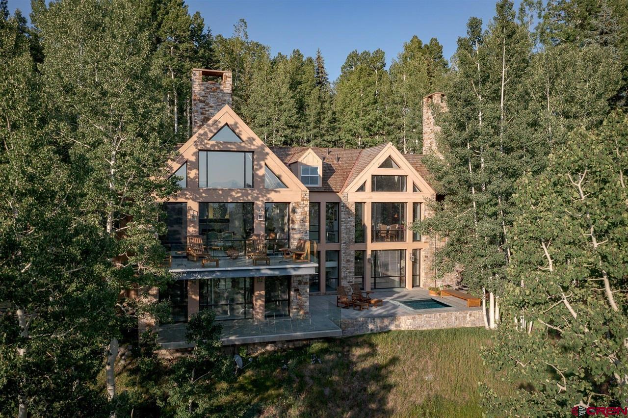 This sun-drenched Aldasoro residence falls into a sea of aspens while gazing out at the iconic Wilson and Sunshine peaks. Renowned architect Hugh Newell Jacobsen conceived this estate on a premier 2.8 acres located in the Telluride mountains. Large walls of glass open onto a cantilevered deck giving you the feeling of being suspended in the trees, while the sounds of the nature and running water in the creek below will bring you into sublime tranquility. As you explore Jacobson's pristine yet comfortable design, you will discover four luxe bedrooms, four and a half baths, and easy indoor/outdoor living with fully custom hot tub & spa. Bonus : a partially finished guest or caretaker apartment over the garage is ready to complete your vision.