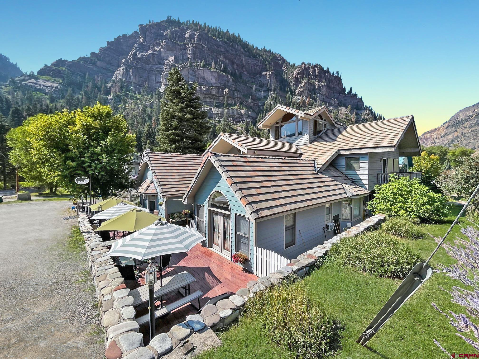 10.5% projected CAP rate in 2021!  This is the best income producing commercial property for sale in Ouray today.  NOW IS YOUR CHANCE to Live/Work/Invest in one of the most beautiful mountain towns in the Rocky Mountain West!   Occupying a premium location just 200 feet from the the Uncompahgre River near the bottom of 6th Avenue in downtown Ouray, the Black Bear Manor has been a successful, established business for almost 30 years...and in 2021 is recording all-time high reservation and revenue numbers.  Purpose built as a Bed & Breakfast (not a retro fitted house), the Black Bear Manor is offered turn-key ready and fully furnished with everything necessary for a smooth take over.    The Black Bear Manor B&B has a solid history of stellar reviews, including a 5 Star Rating and a Certificate of Excellence from TripAdvisor. Repeat guests are common and updated books supports asking price with a strong CAP.   Center of town location on 6th Avenue makes for an easy walk to downtown shopping and restaurant district, as well as the new Ouray Via Ferrata and the world-famous Ouray Ice Park.   This property features:  • 1696 sq. ft. wrap-around deck with picnic tables, a porch swing, umbrellas, café-style outdoor seating, and a 24-hour guest hot tub.  • 3rd Floor Observatory/game room provides a panoramic view of the surrounding cliffs and mountain peaks, including the Amphitheater, Mt. Hayden, US Mountain and Mt. Abrams, just to name a few.  • On-site and off-site parking. • 100-year multicolored, concrete tile roof. • Nine fully furnished, uniquely decorated guest rooms, some with fireplaces and whirlpool tubs.  • Owner/Manager quarters could be converted into a 10th guest room if so desired. • All rooms feature their own private bathroom and external entrance for convenience and easy ingress/egress. • Owner/Manager quarters could be converted into a 10th guest room if so desired • Large laundry Room with Commercial Dryer • Large basement for storage, a workshop, or futu