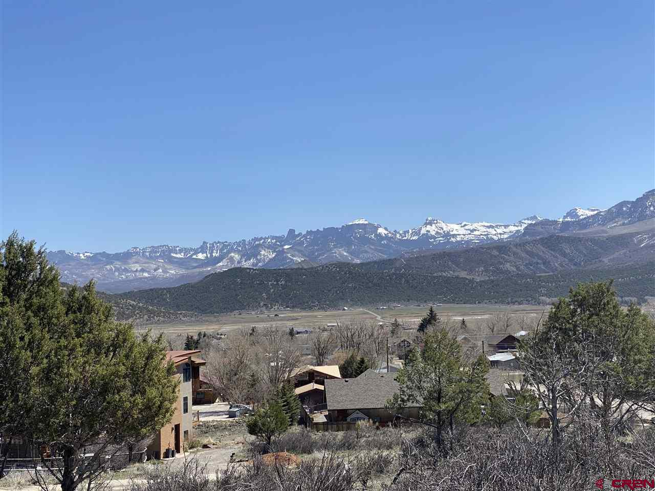 Beautiful oversized Town lot! This piece of property looks over the Town of Ridgway, with un-obstructed and sweeping views of the Cimarron Mountain Range and Uncompaghre Valley. This property offers tons of privacy from neighbors with it measuring 14,288 sq. ft., compared to most Town of Ridgway lots of 7,100 sq. ft.  The subdivision has paved roads, curb, gutters, and sidewalks already in place. Partial water and sewer taps paid.  Enjoy being within walking distance to Downtown Ridgway and Ridgway Elementary School. Come take a look and build the house of your dreams!