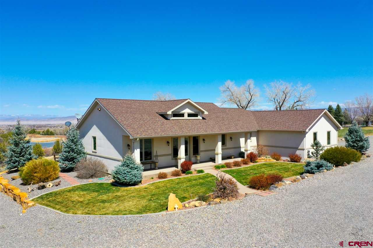 This beautiful 4+ acre irrigated Spring Creek property is located in one of the most desirable areas in the Uncompahgre Valley. There are views in all directions, from the mountains to the valley. The home was built in 2012 and offers a great open floor plan with numerous windows for natural lighting and in floor radiant heat for those cold winter nights. The tongue and groove ceilings are accented throughout the home. The kitchen has granite counter tops with under the cabinet lighting, a kitchen bar, and dining area. The master bedroom has his-and-her walk-in closets, double vanity, soaking tub and custom walk-in shower. The large covered deck overlooks the natural landscaping that includes several large trees and a pond. One of the many amenities of this property are the gorgeous views of the Uncompahgre Valley from the deck. In addition to the home's oversized 2-car attached garage, there is a large detached garage/shop with two 12x10 overhead doors. Bunkhouse and RV shed with hookups, and plenty of room for horses or other animals on the 2.5 irrigated acres of grass pasture. There is a lot more to this property than we can describe -- a must-see to appreciate!