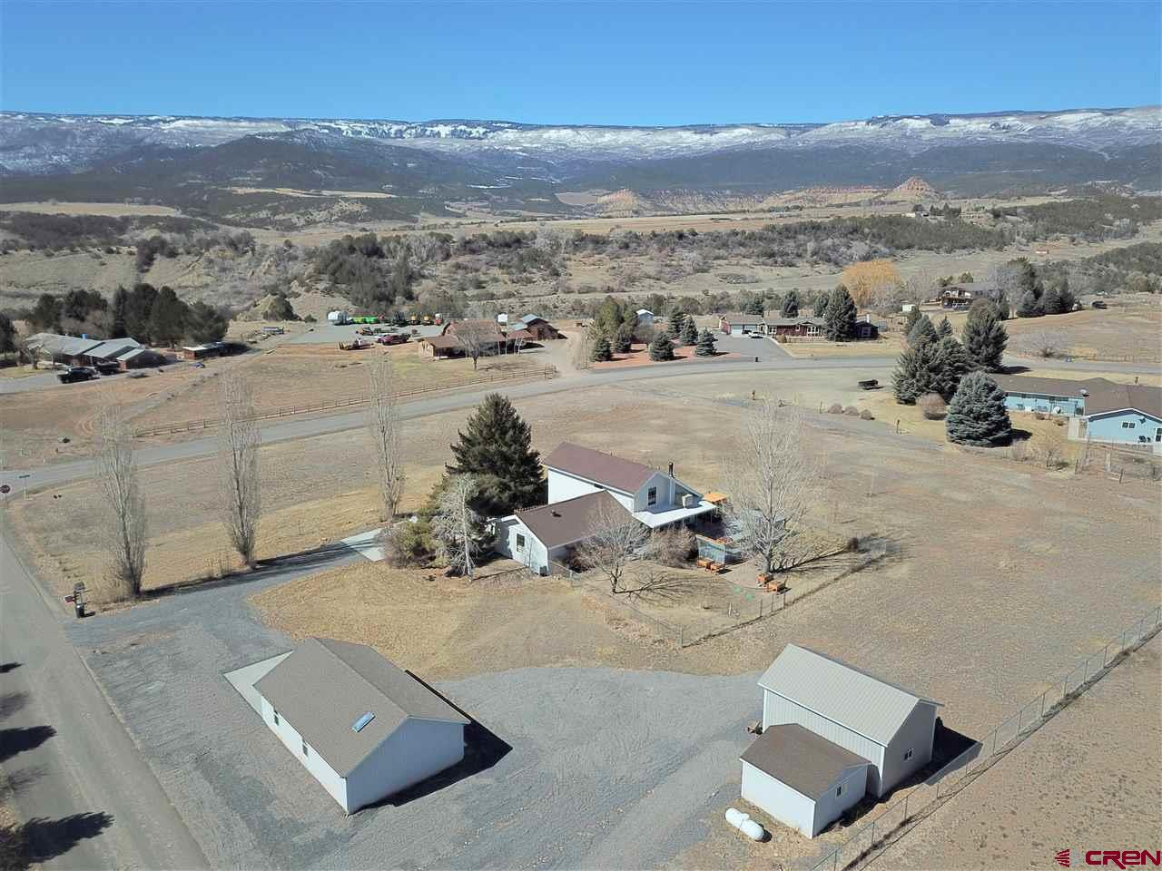 Beautiful home situated on 2.2 acres with outstanding Grand Mesa views! This home offers many wonderful features including  tongue-n-groove ceiling, newer Renewal windows by Anderson, gas fireplace and a floor plan that offers great flex spaces. Lovely kitchen with Quartz countertops, pantry, newer appliances and open to the dining room and an office. Master bedroom on the main level with two more bedrooms and full bathroom upstairs. A finished basement with large family room, pellet stove, full bathroom, two bedrooms and utility/laundry room. Enjoy your Colorado days on the back deck with room to entertain or a night under the stars in the hot tub.  Awesome workshop and garage spaces! A two car attached garage, two car detached garage plus a camper/large vehicle garage. Mature trees and landscaping under a sprinkler system with irrigation water through the HOA. A country location yet close to town! Elevate fiber internet is installed at the home.