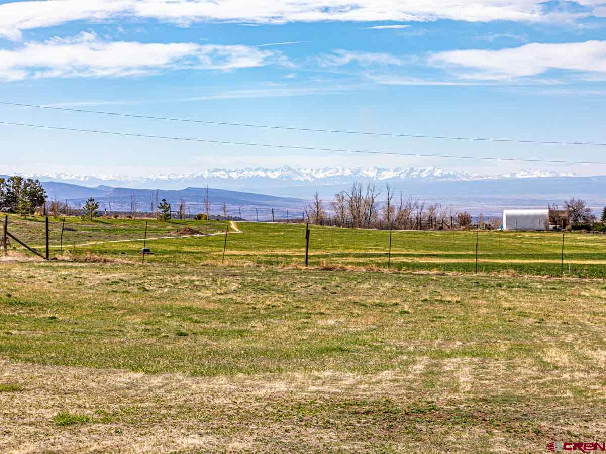 This 4.45 acre country lot is located near Cedaredge, Colorado. The lot sits in a beautiful country setting that is surrounded by orchards and fields and boasts beautiful views of the Grand Mesa, Surface Creek Valley and the San Juan Mountains. Currently this large lot is set up for 3 separate mobile units with water, sewer and electricity to each location. This allows for numerous options including a place to park your RV while you build or rentable income on the 3 spaces, however a mobile home permit is required if 3 or more spaces are rented. The property is nicely fenced and tidy and outbuildings include a shed with laundry facility's and a green house. The country lot has a well and a domestic water tap, electricity and a newer septic that is sized for a large home.