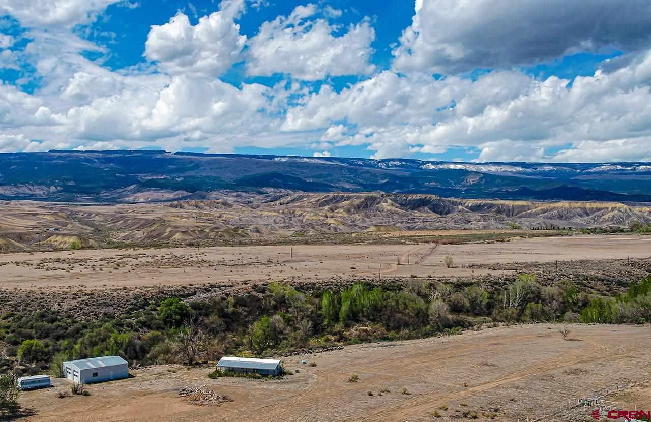 "Land, views, water and all utilities available, what more can you ask for! With all utilities available and 4 shares of irrigation water from Fogg ditch, you can come build your dream home and stay in the single wide until completion, bring your animals/livestock or grow, the options are endless with this property. Property is being sold ""as is"" and everything stays with property including 70's pull behind camper with title."