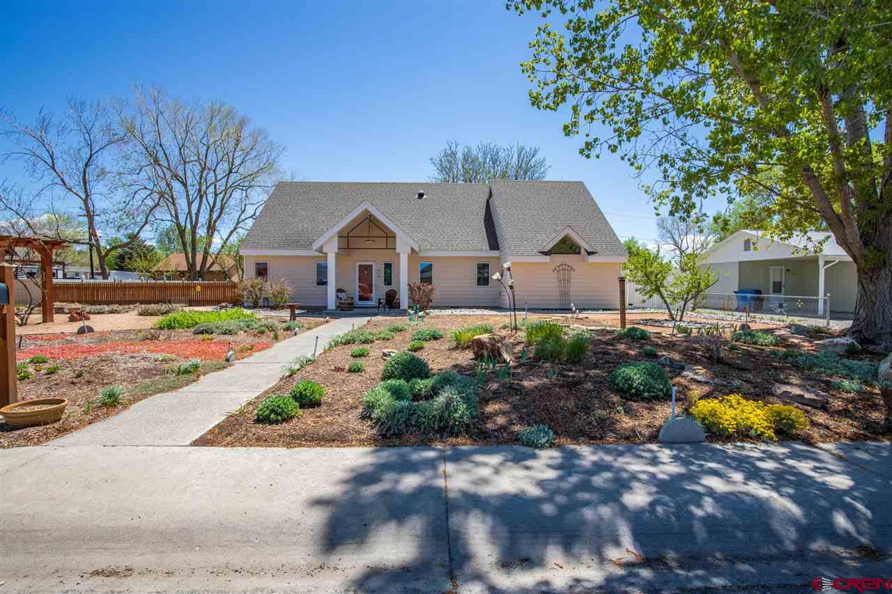 This home has it all! The minute you pull up to the property you will notice the remarkable landscaping, thoughtfully planned with different types of low water foliage that bloom and blossom at different times of the growing seasons. There is pergola sitting area in the middle of the front yard garden oasis perfect for enjoying cool summer evenings. When you enter the home you will be impressed by the immediate beauty of the open living space with the natural light flowing in the windows showcasing the hard surface flooring and high ceilings. Through the living room area is the dining room with grand windows giving the space an airy feel that flows into the attractively remodeled kitchen with lots of countertop and cabinet space. Off of the kitchen, there is a generous laundry area, a built in office space and a powder room making the best use of this lovely space that circles around through to a large family room. The bedroom suite is privately located in a separate wing off of the main living area with access to the back yard patio and its own mini split heating and cooling system adding to the comfort of this space. The bedroom suite has so much room to store all of your necessities with the large walk in closet and double door linen storage. Up the hand crafted antique wood stairs you will find the other full bathroom, and three great sized bedrooms, all with their own unique characteristics. If that is not enough to make your heart melt there are a few little stairs that lead up to an adorable attic room with a solar tube giving the space some natural light. The current owners use this space as a non conforming bedroom for their creative teen, but the possibilities are endless. This home is not lacking in style, beauty and functionality, and the outdoor space is no exception. This home sits on an oversized lot with extra parking and alley access to the two story, double car detached garage. Complete with a fully finished and insulated wood shop on the second le